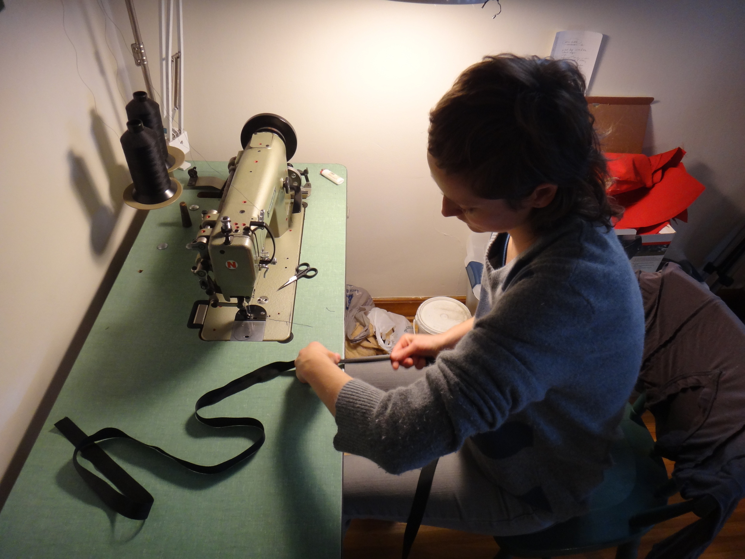The Artist prepares grosgrain trim to add as the final touch to a Calf Pack ( leather blade.com ).