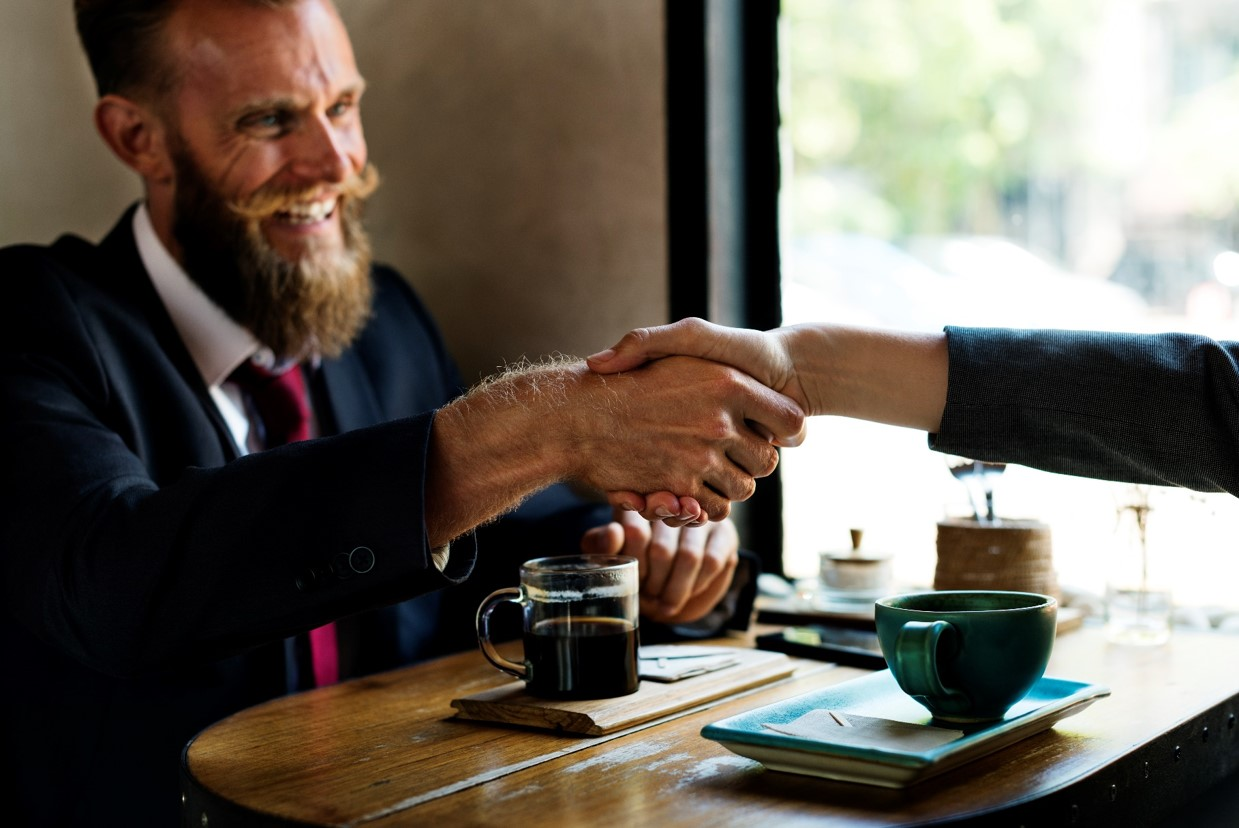 business handshake over coffee compressed.jpg
