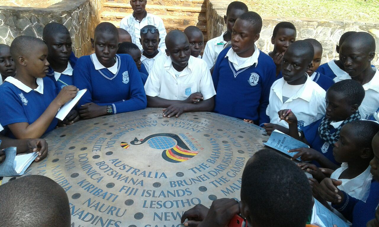Pupils learning about the countries named on the commonwealth stone near the source of the River Nile.
