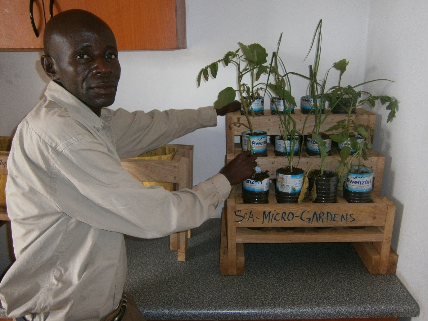 Bosco, one of the CHPs in Bukasakya, displaying micro garden. We are able to grow onions, carrots, beets and other veg