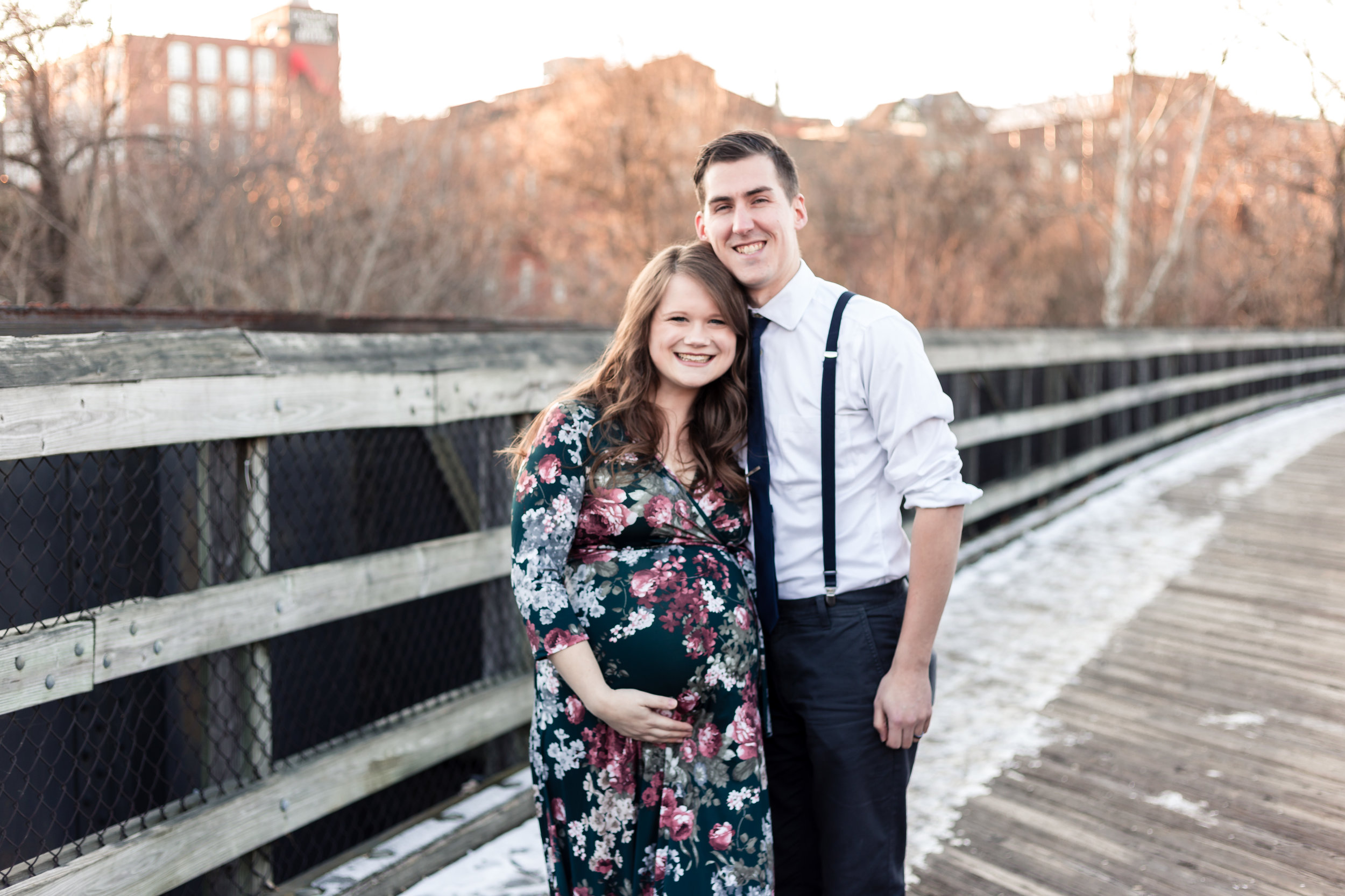 Couple poses together on bridge in downtown Lynchburg while mother cradles pregnant belly.