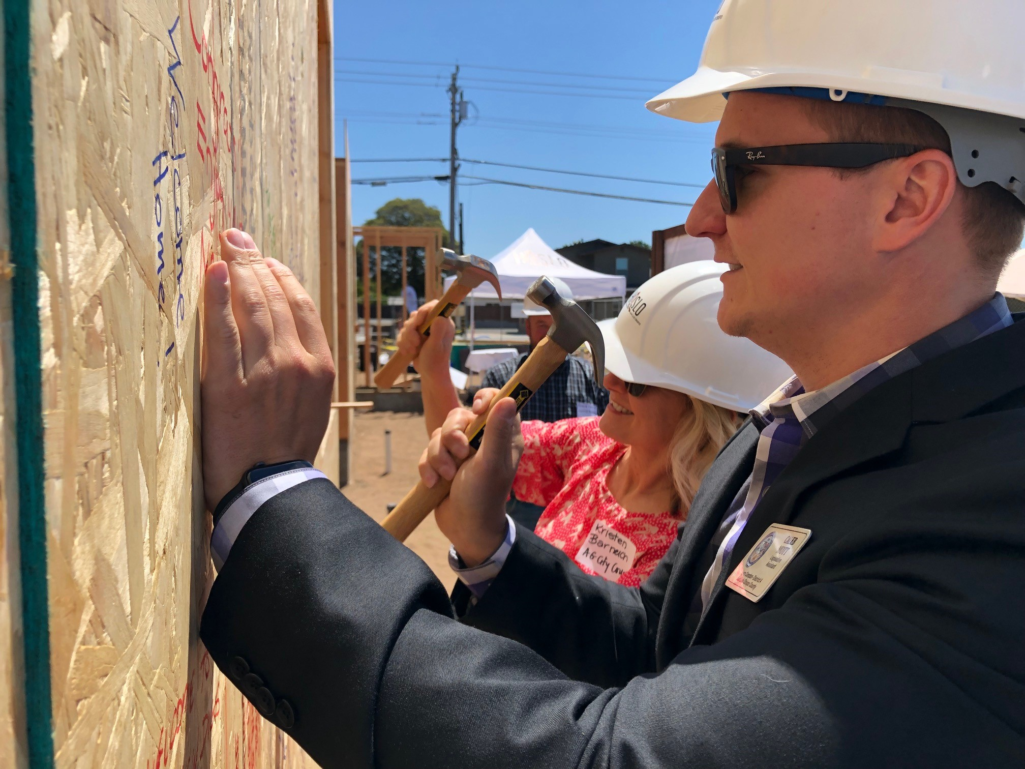 "Arroyo Grande Mayor Pro Tem Kristen Barneich and Caleb Mott, Legislative Assistant to District 4 County Supervisor Lynn Compton, hammer the ""Best Wishes"" board onto the building."