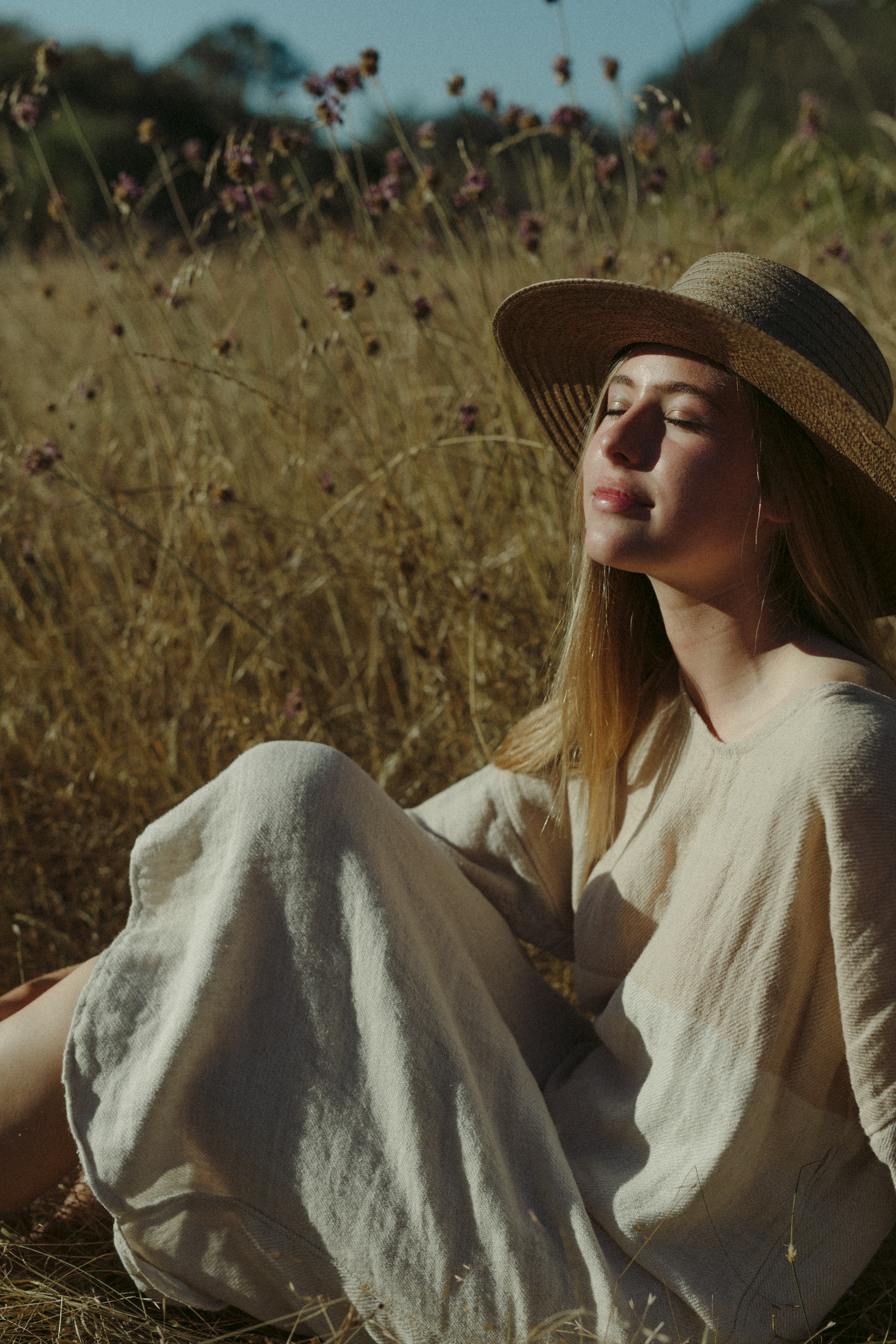 girl in a grass field in a straw hat, fashion photography, handwoven clothing woven wares victoria bc