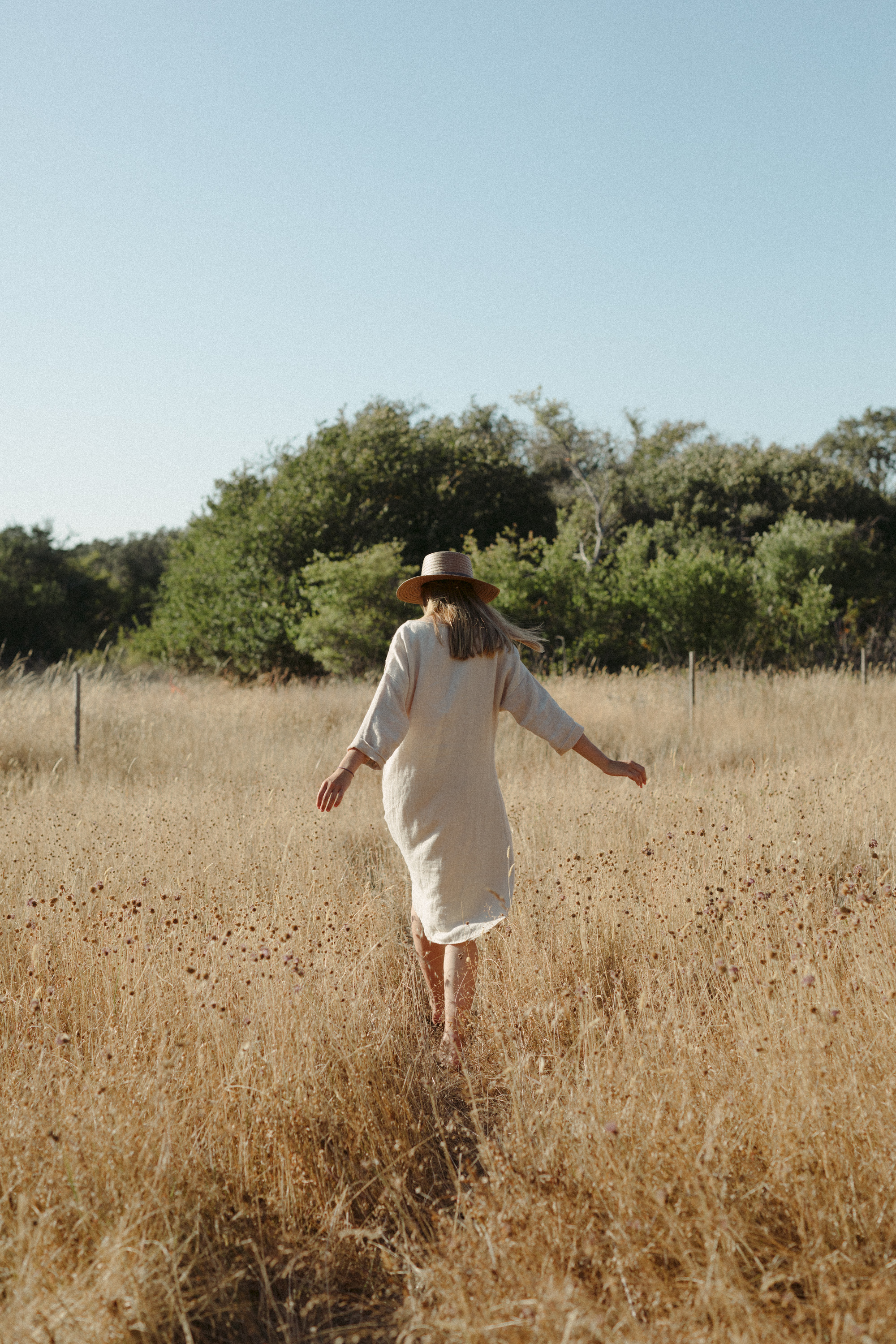 girl running in a grass field, fashion photography, handwoven clothing woven wares victoria bc