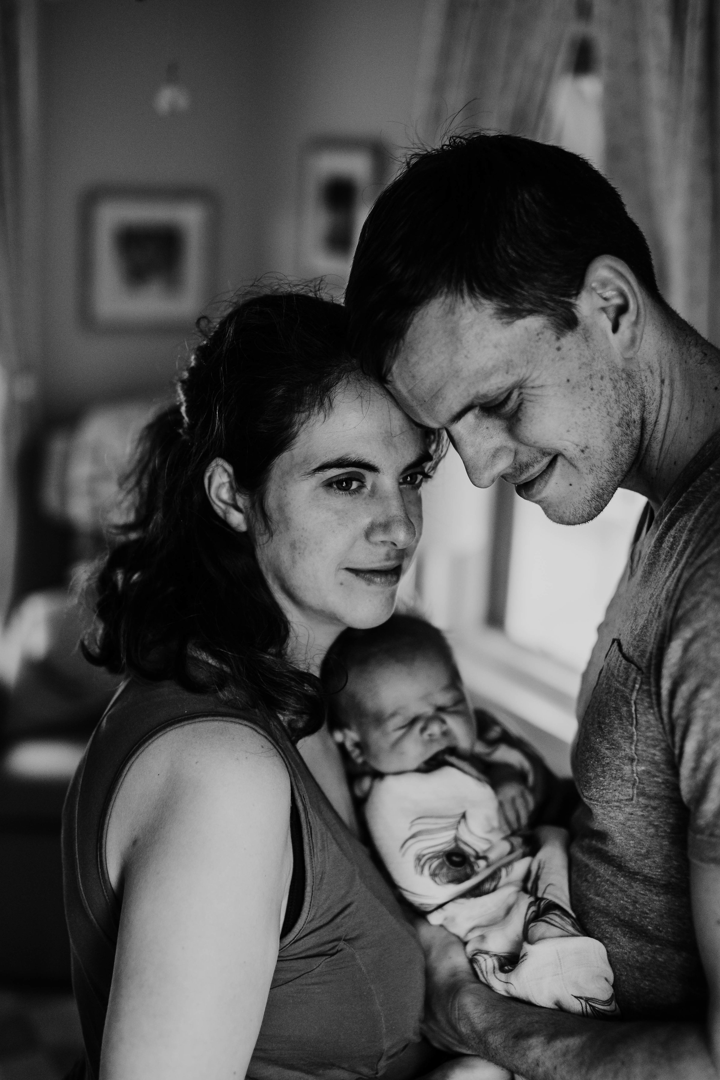 A moment of peace with the whole family before the window in black and white | Paul O Lifestyle Newborn Session | Hannahill Photogrraphy | Kansas City, MO | Family photography in home