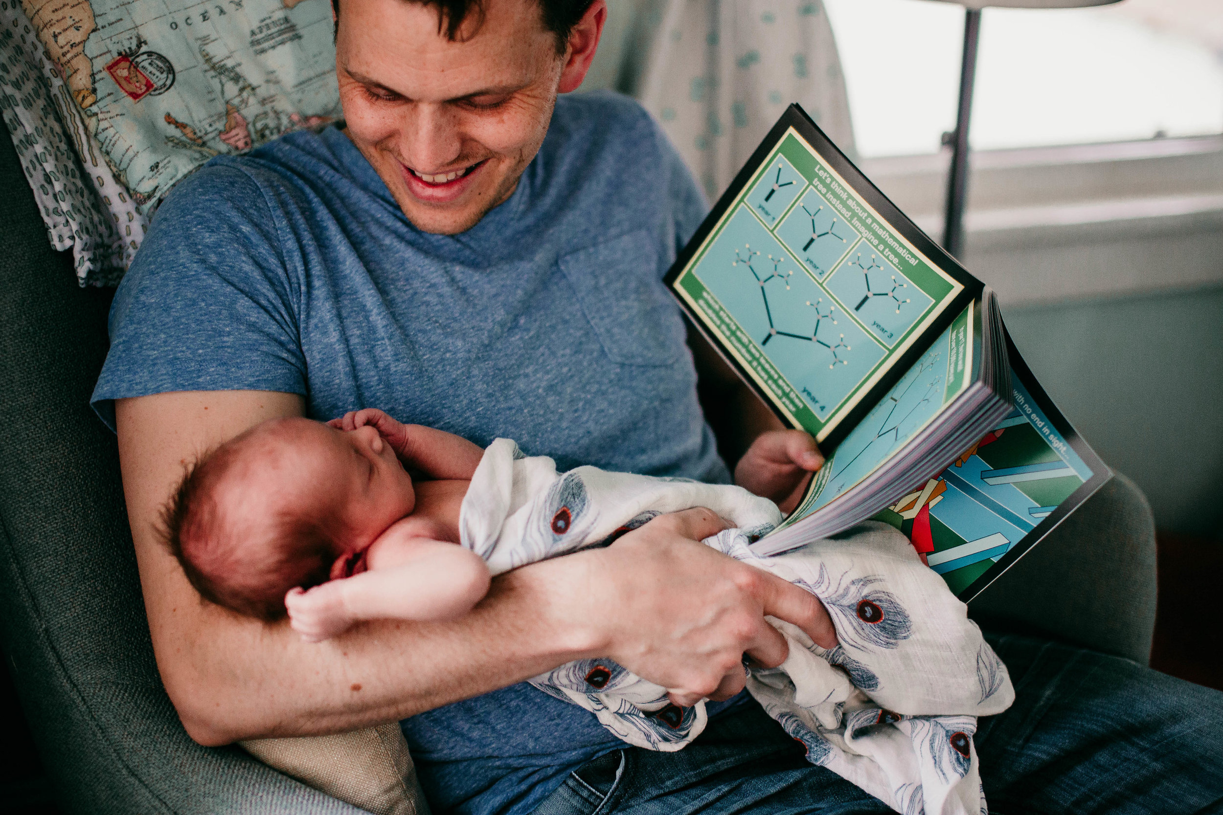 Father and son moment reading a book a bout math | Paul O Lifestyle Newborn Session | Hannahill Photogrraphy | Kansas City, MO | Family photography in home