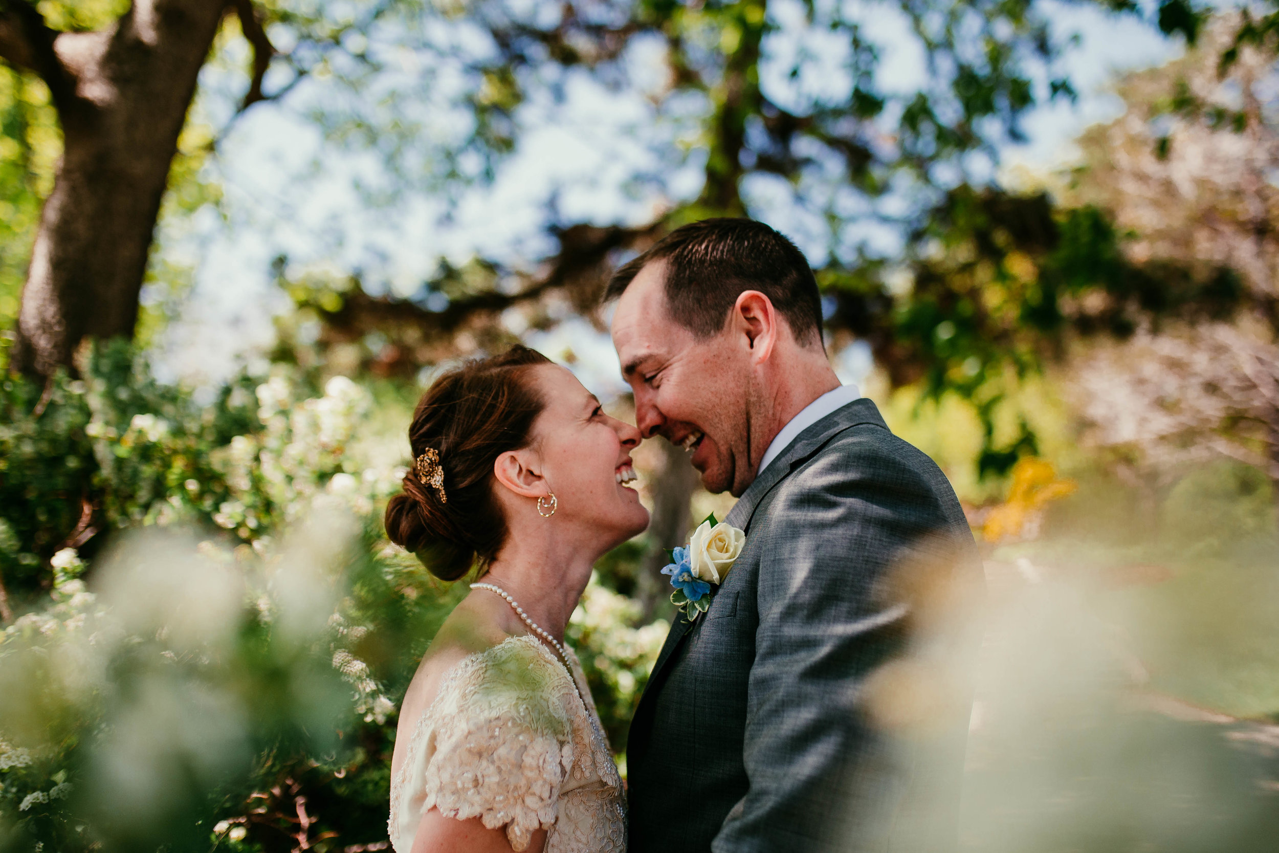 Bert & Lauren's North Kansas City Spring Wedding | Hannahill Photography | Raleigh Durham Photographer | North Carolina Wedding Photography | Family Photographer | Wedding photographer | The couple laughs together amidst spring bushes