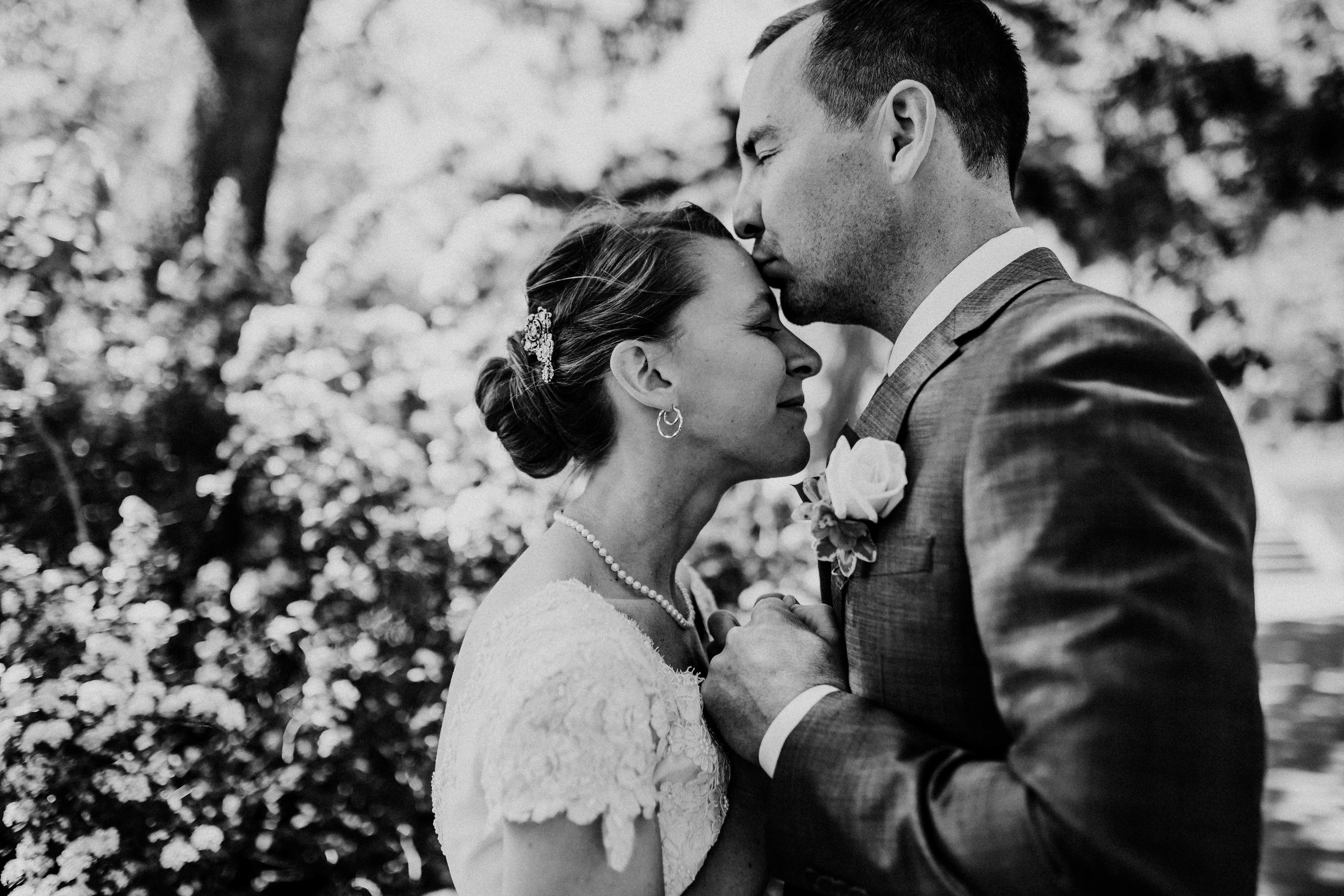 Bert & Lauren's North Kansas City Spring Wedding | Hannahill Photography | Raleigh Durham Photographer | North Carolina Wedding Photography | Family Photographer | Wedding photographer | Groom kisses bride on the forehead in black and white portrait