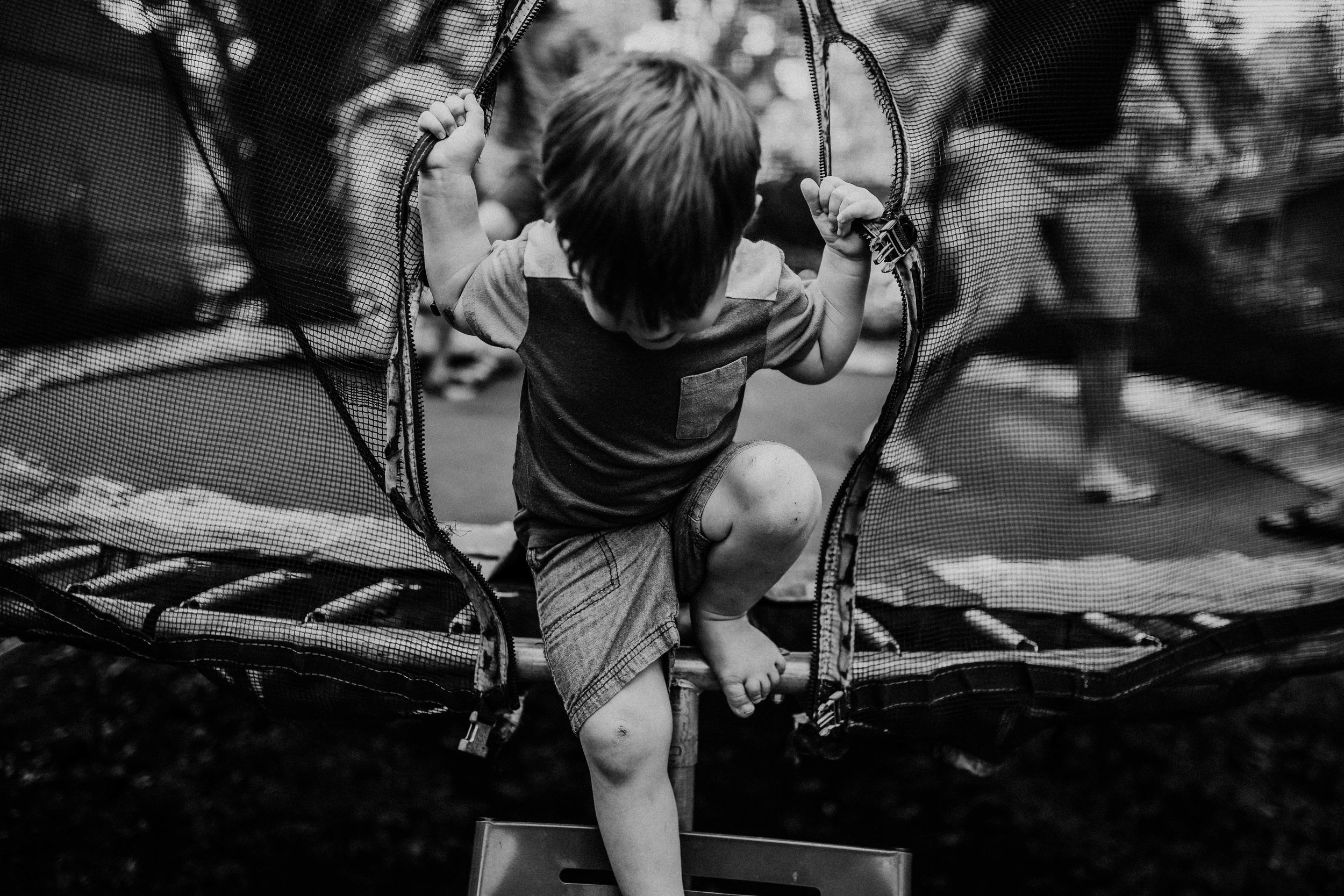The youngest little boy climbs off the trampoline.  The Carter Family : Summer in the Backyard | Hannahill Photography | Kansas City, MO | Family photography lifestyle photographer | Wedding photographer Durham North Carolina Raleigh | Birth photographer Documentary