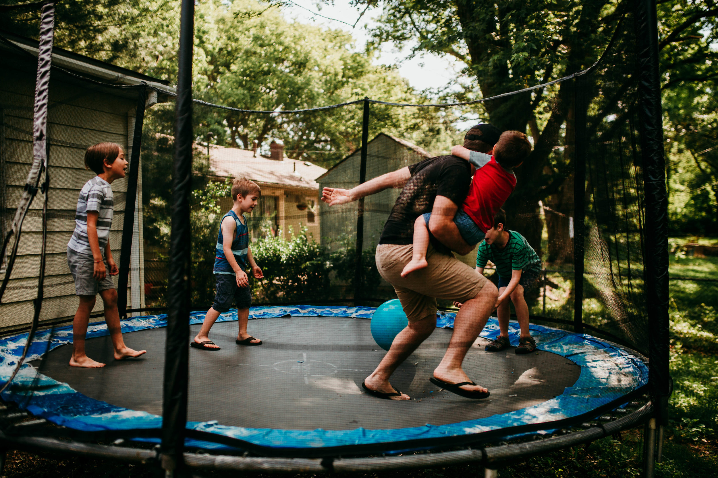 Dad and all the little boys play with a ball on the trampoline.   The Carter Family : Summer in the Backyard | Hannahill Photography | Kansas City, MO | Family photography lifestyle photographer | Wedding photographer Durham North Carolina Raleigh | Birth photographer Documentary