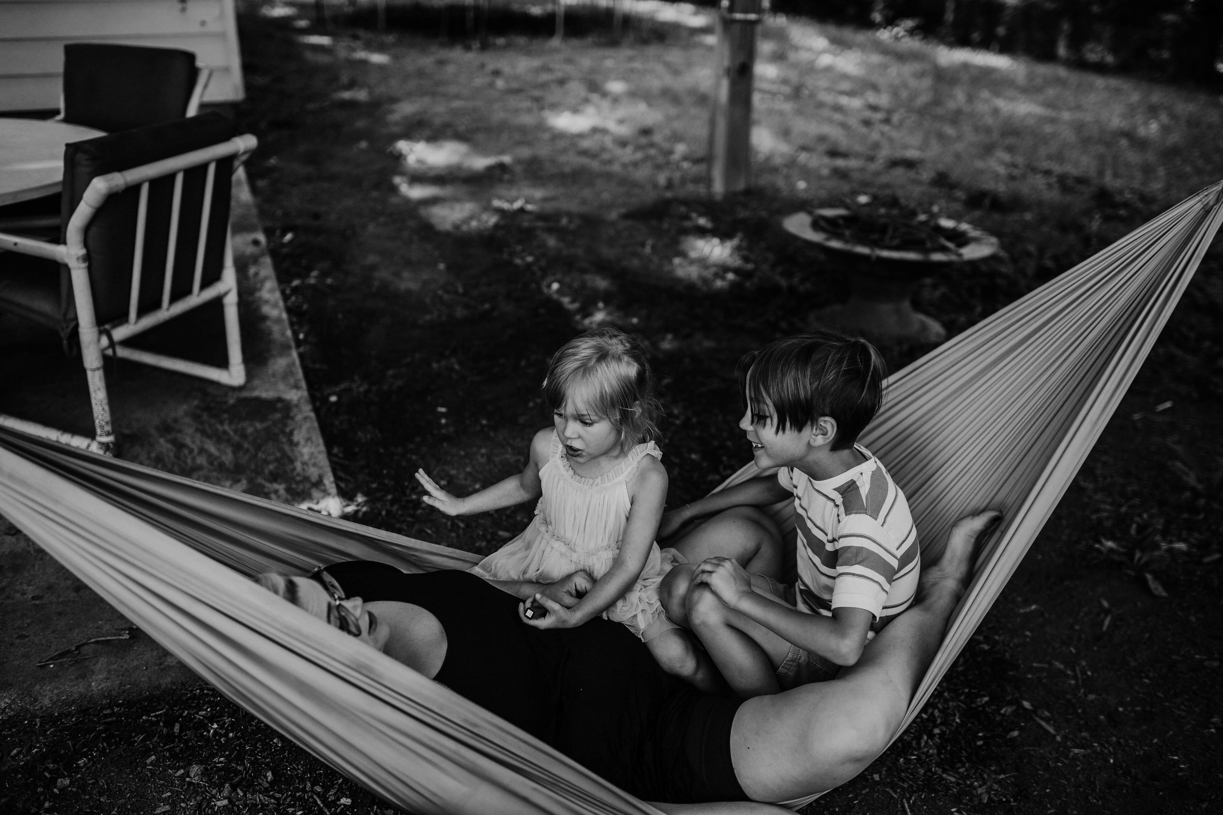 Mom and two of her kiddos sitting on the hammock, the young  daughter is explaining something very intense to mom.   The Carter Family : Summer in the Backyard | Hannahill Photography | Kansas City, MO | Family photography lifestyle photographer | Wedding photographer Durham North Carolina Raleigh | Birth photographer Documentary