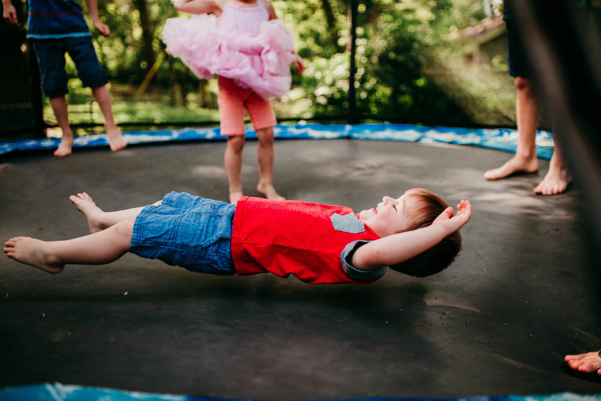 The littlest son getting bounced on the trampoline.   The Carter Family : Summer in the Backyard | Hannahill Photography | Kansas City, MO | Family photography lifestyle photographer | Wedding photographer Durham North Carolina Raleigh | Birth photographer Documentary