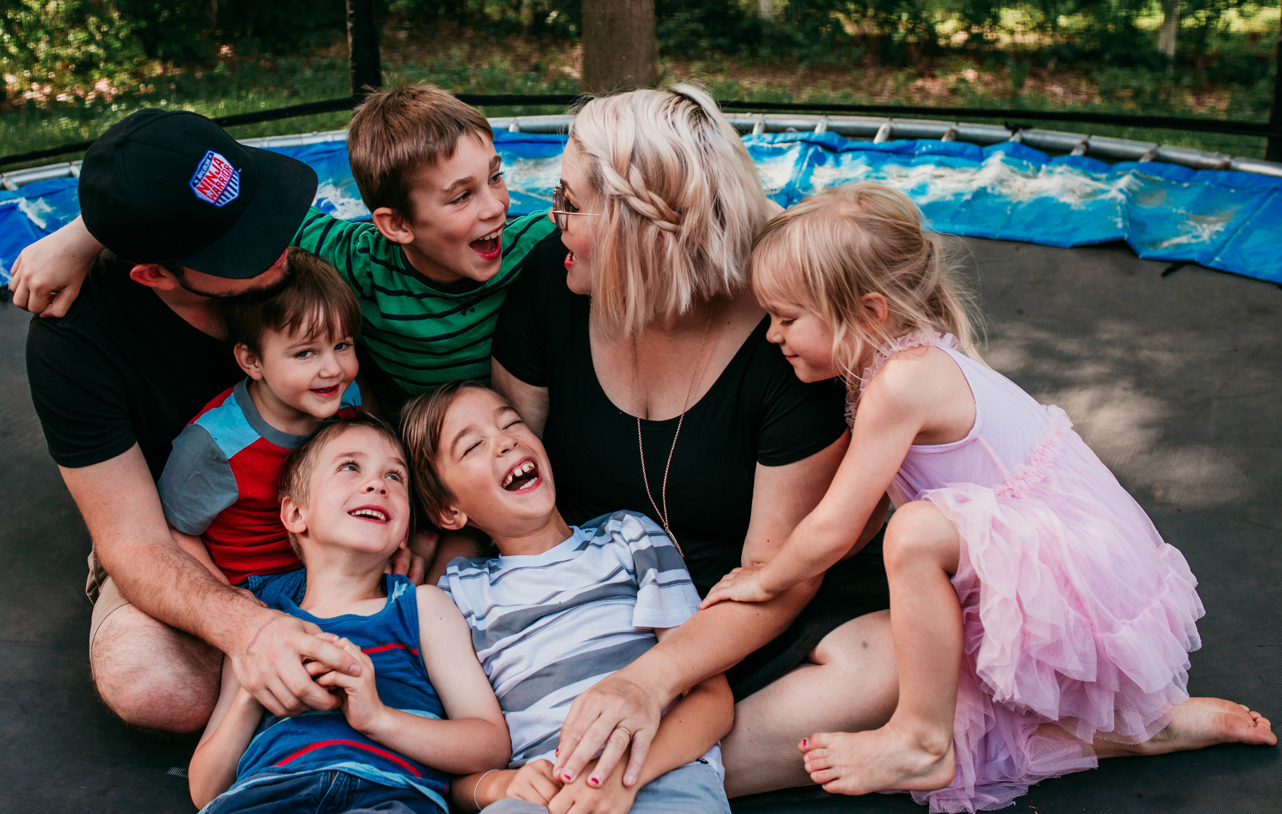 The family gathers together on the trampoline laughing about something silly.   The Carter Family : Summer in the Backyard | Hannahill Photography | Kansas City, MO | Family photography lifestyle photographer | Wedding photographer Durham North Carolina Raleigh | Birth photographer Documentary