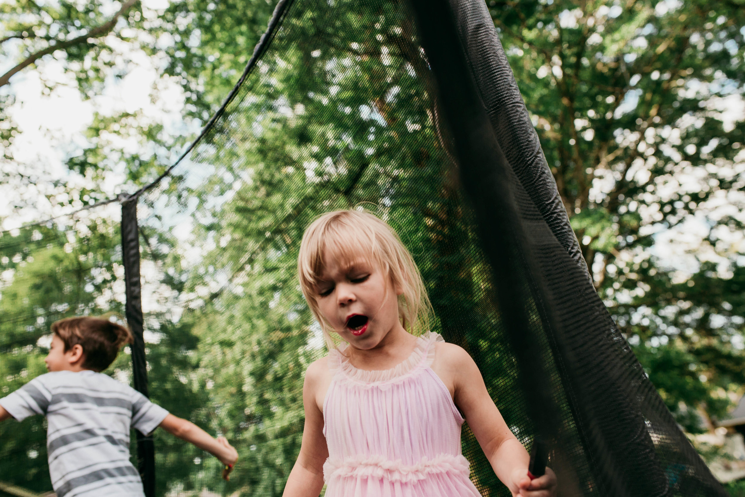 The little girl talks loudly as she walks around the trampoline.   The Carter Family : Summer in the Backyard | Hannahill Photography | Kansas City, MO | Family photography lifestyle photographer | Wedding photographer Durham North Carolina Raleigh | Birth photographer Documentary
