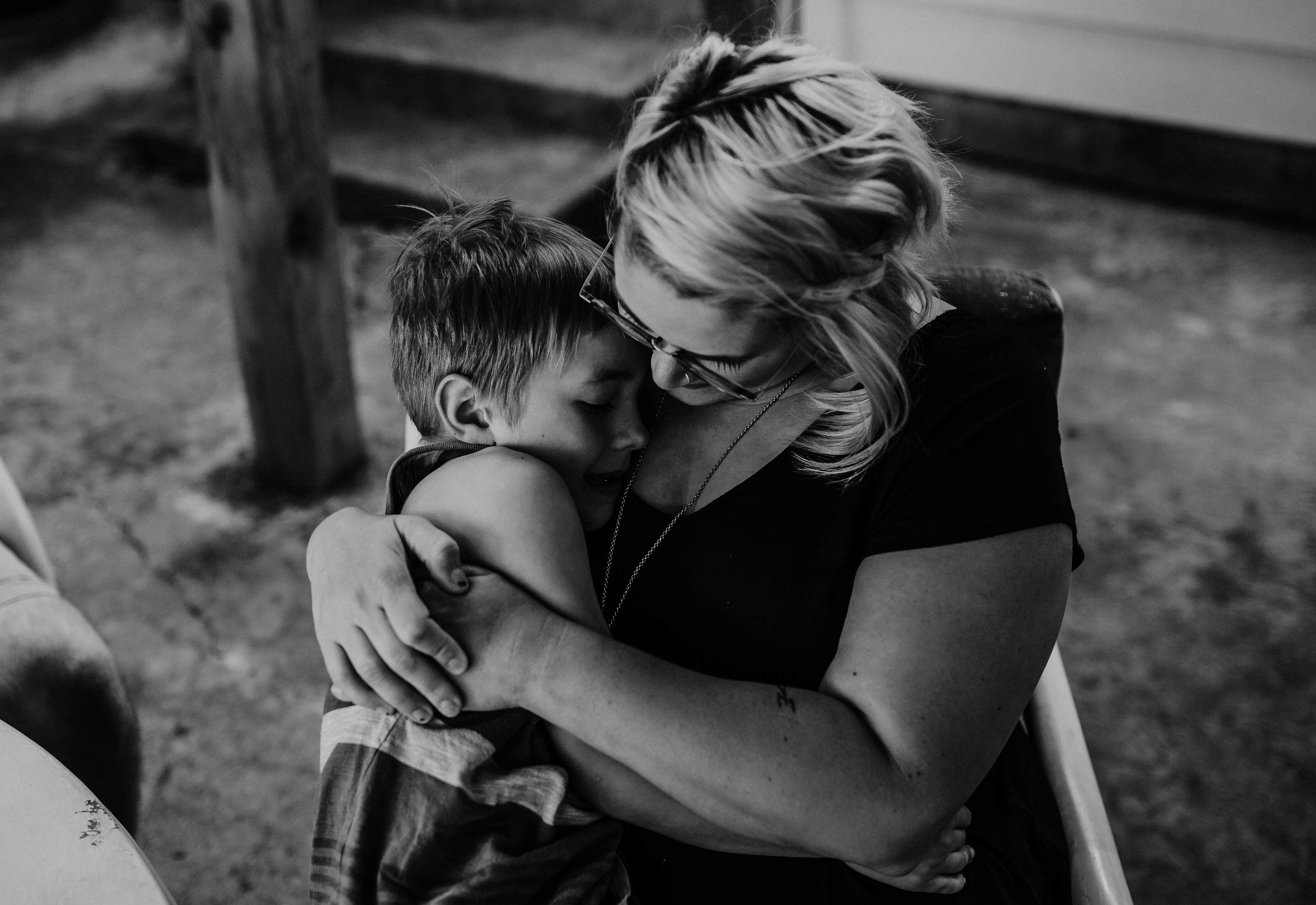 Mom cuddles her son in black and white  The Carter Family : Summer in the Backyard | Hannahill Photography | Kansas City, MO | Family photography lifestyle photographer | Wedding photographer Durham North Carolina Raleigh | Birth photographer Documentary