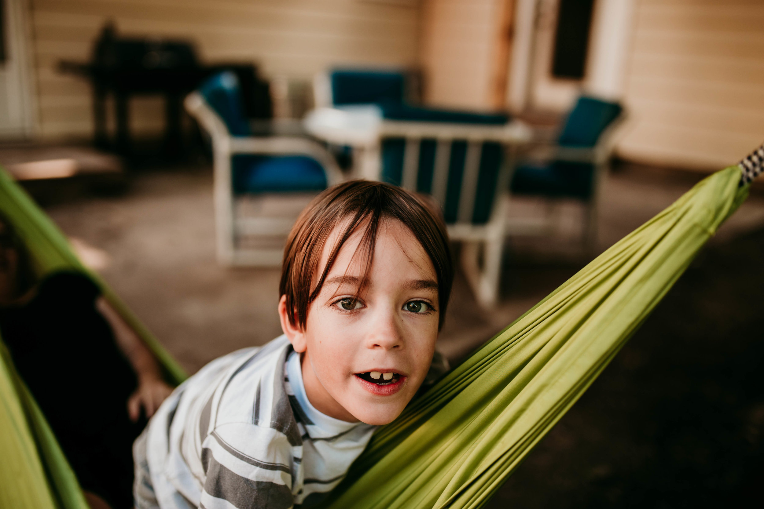 one son climbing on the hammock with his mother.  The Carter Family : Summer in the Backyard | Hannahill Photography | Kansas City, MO | Family photography lifestyle photographer | Wedding photographer Durham North Carolina Raleigh | Birth photographer Documentary