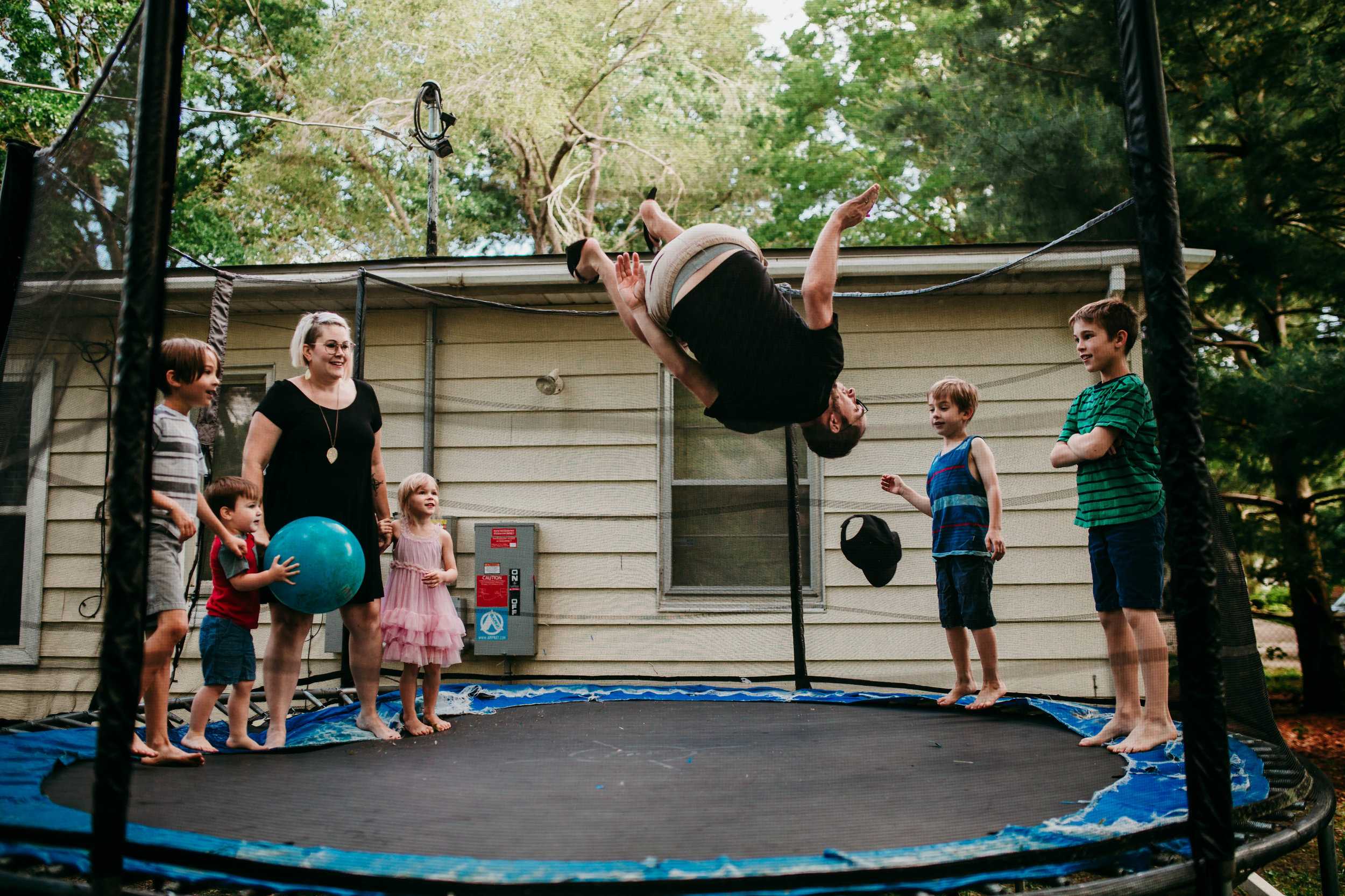 Watching dad jumping on the trampoline.   The Carter Family : Summer in the Backyard | Hannahill Photography | Kansas City, MO | Family photography lifestyle photographer | Wedding photographer Durham North Carolina Raleigh | Birth photographer Documentary