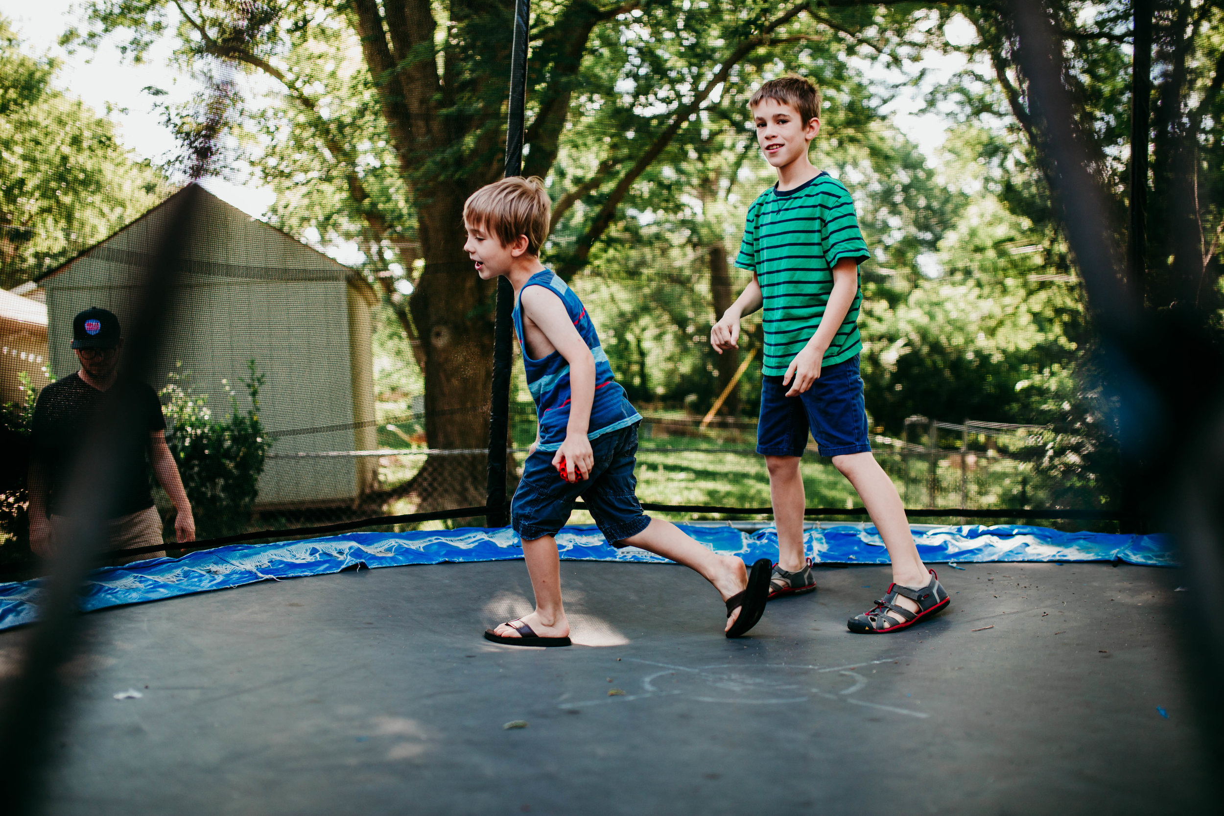 The two oldest sons running on the trampoline.   The Carter Family : Summer in the Backyard | Hannahill Photography | Kansas City, MO | Family photography lifestyle photographer | Wedding photographer Durham North Carolina Raleigh | Birth photographer Documentary