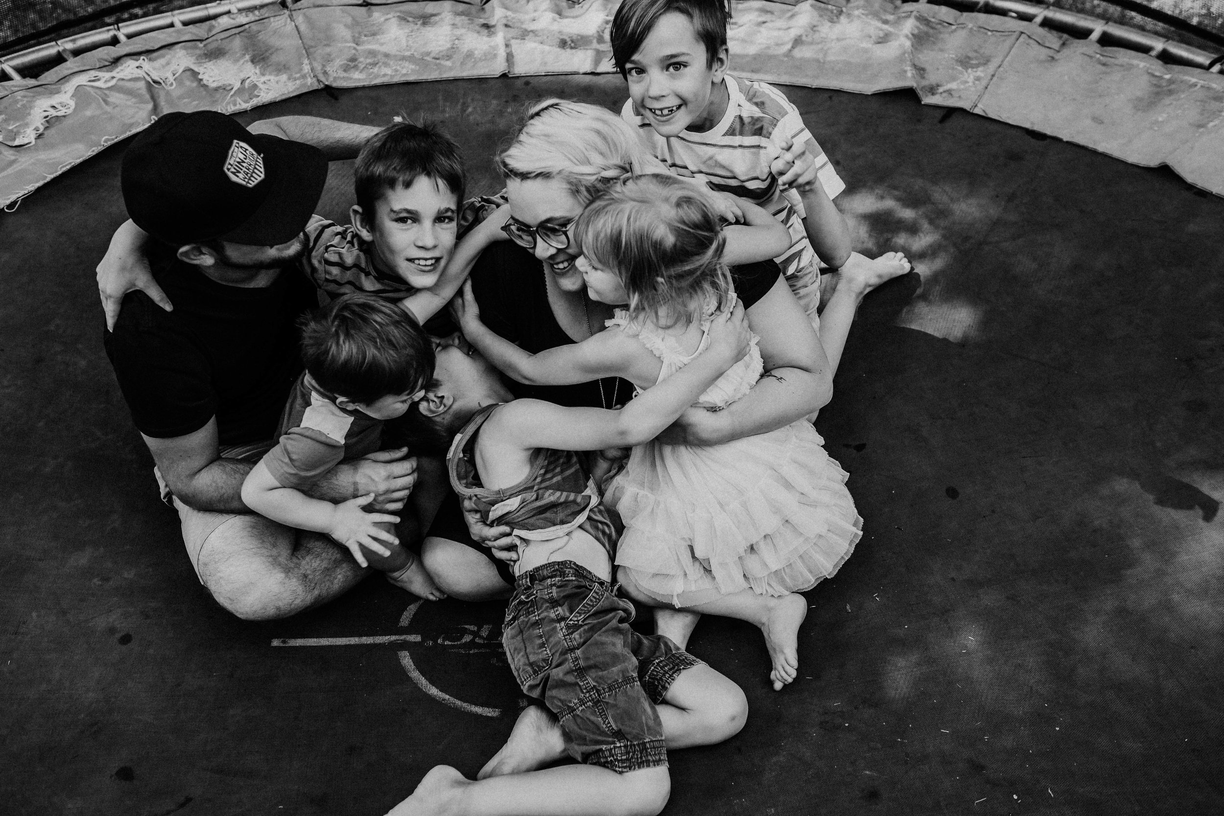 The family laughing and cuddling together on the trampoline in black and white.  The Carter Family : Summer in the Backyard | Hannahill Photography | Kansas City, MO | Family photography lifestyle photographer | Wedding photographer Durham North Carolina Raleigh | Birth photographer Documentary