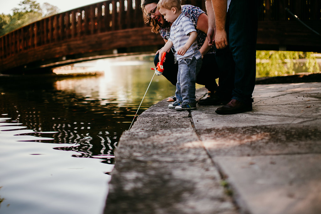 The family by the pond pretending to fish at the Loose Park | The Hann Family | Hanna Hill Photography | Durham, NC Family photographer