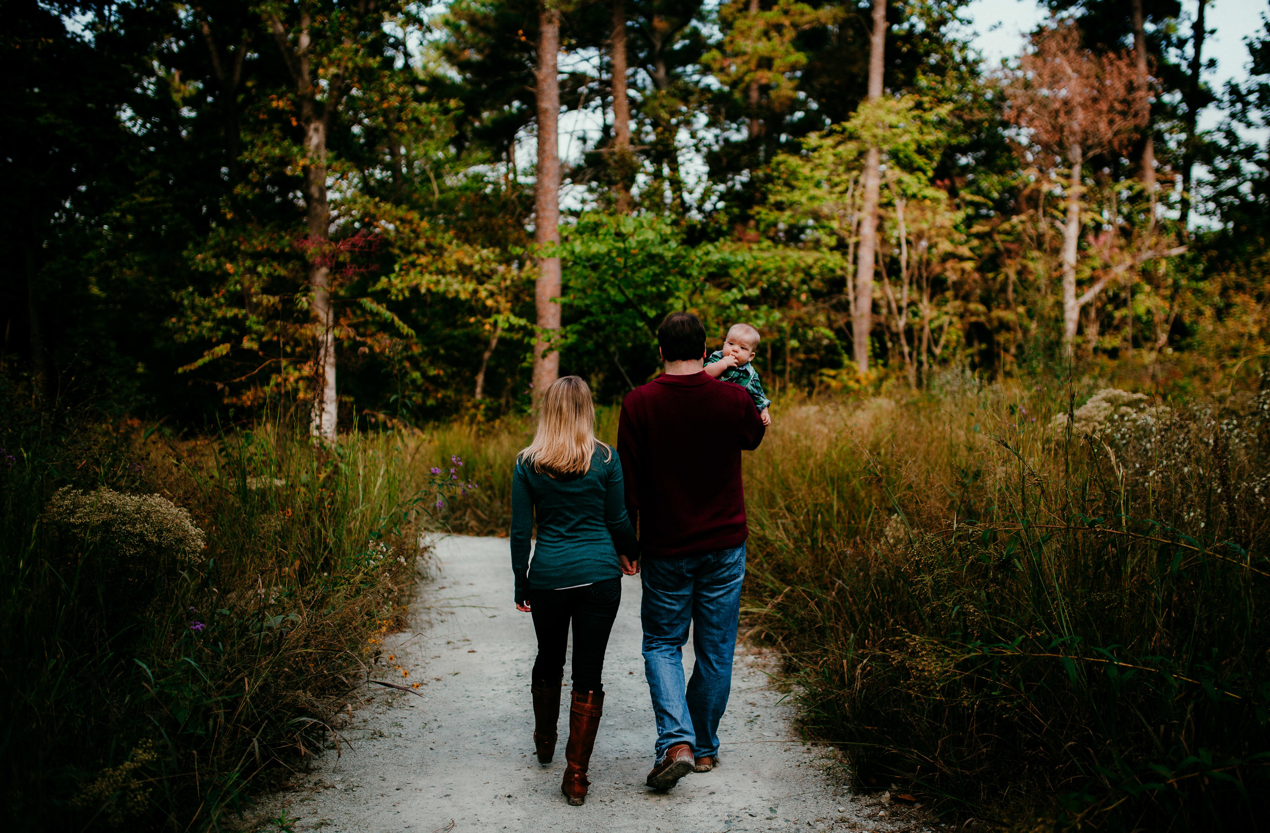 mom and dad and baby walking amongst colorful trees during their Fall family session at Duke Gardens in Durham North Carolina | Hanna Hill photography | Raleigh birth and family photographer