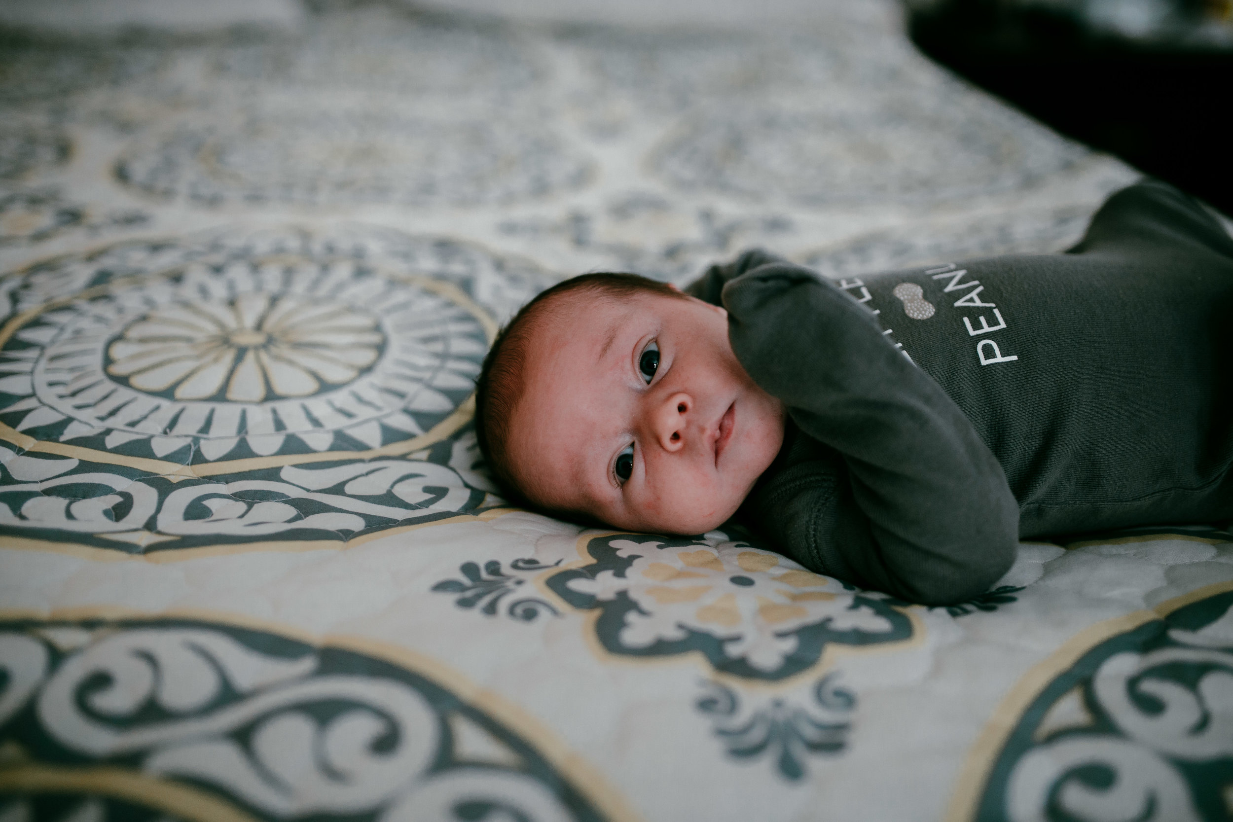 sweet little newborn on the bed staring at the camera during an lifestyle in home newborn session | Hanna Hill Photography | Raleigh birth and family photographer | Raleigh newborn photographer