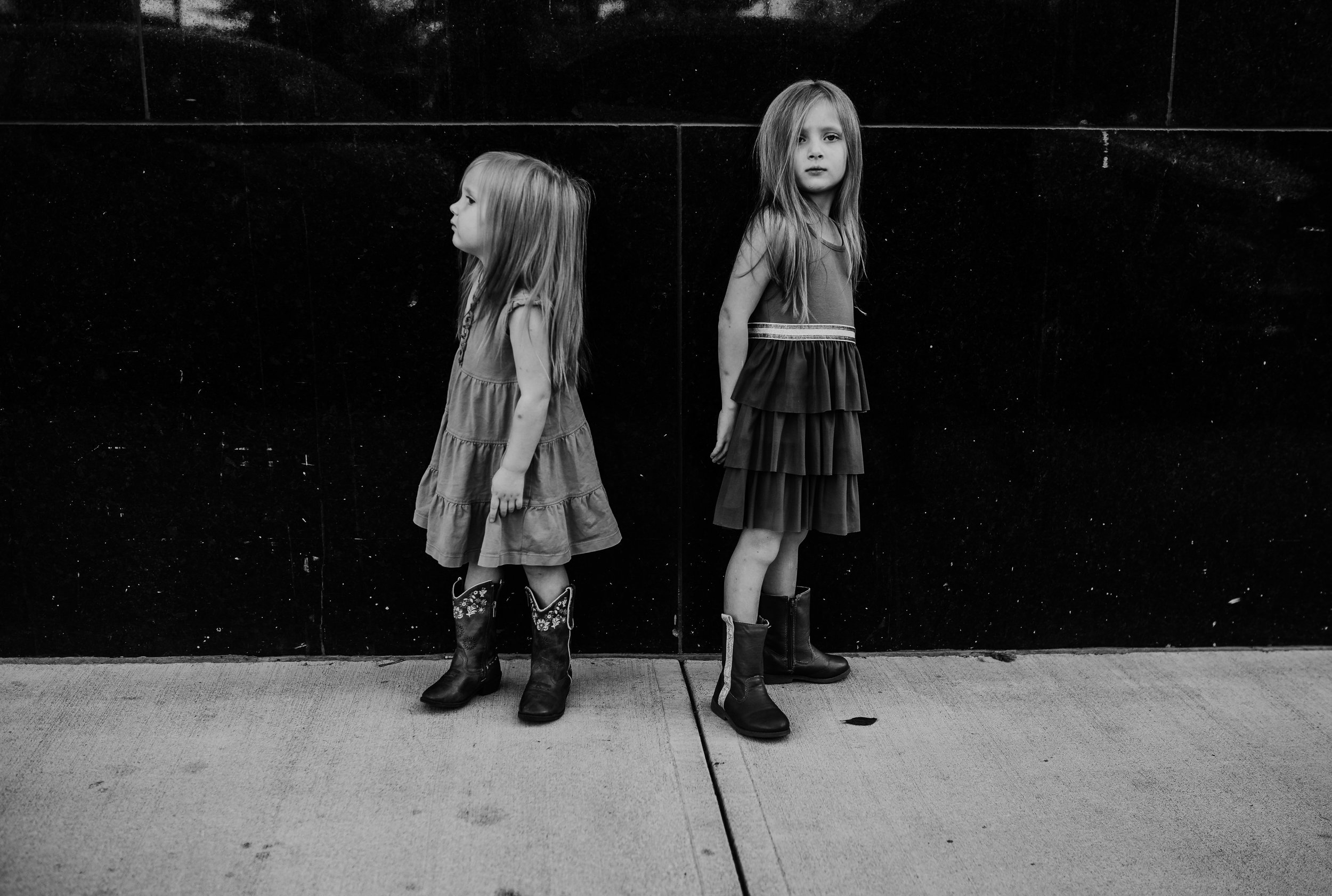 two sisters standing in downtown durham during their family photography session | Hanna Hill Photography | Raleigh birth and family photographer
