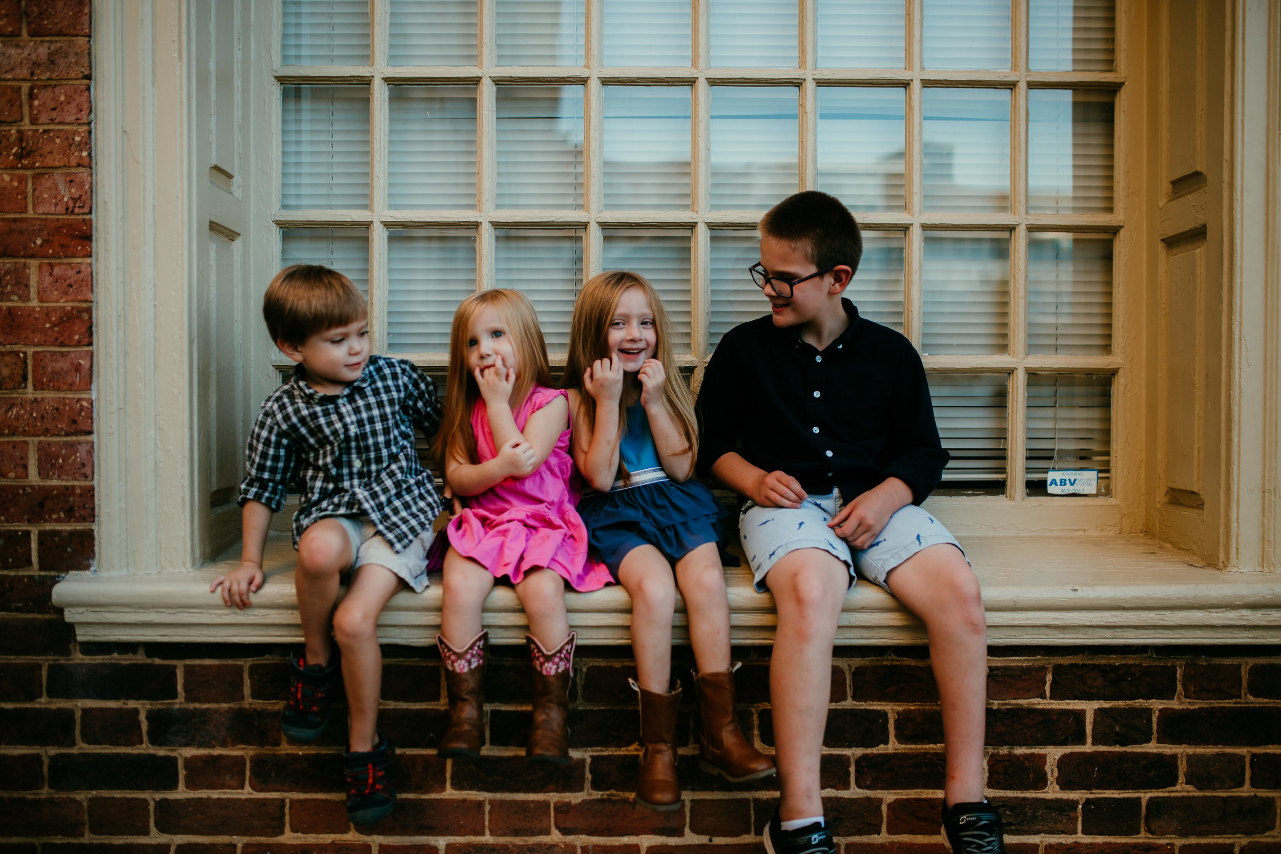 the siblings sitting on a window sill during their downtown durham, NC family photography session | Hanna Hill Photography | Raleigh birth and family photographer
