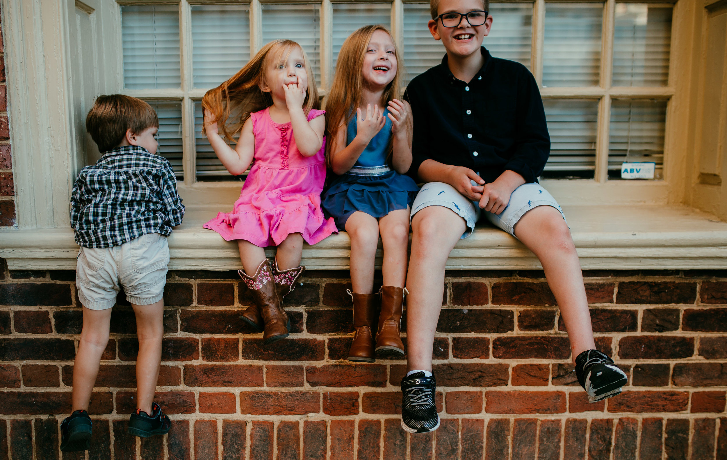 siblings sitting on a window sill during their family photography session in downtown durham, NC  Hanna Hill photography | Raleigh birth and family photographer