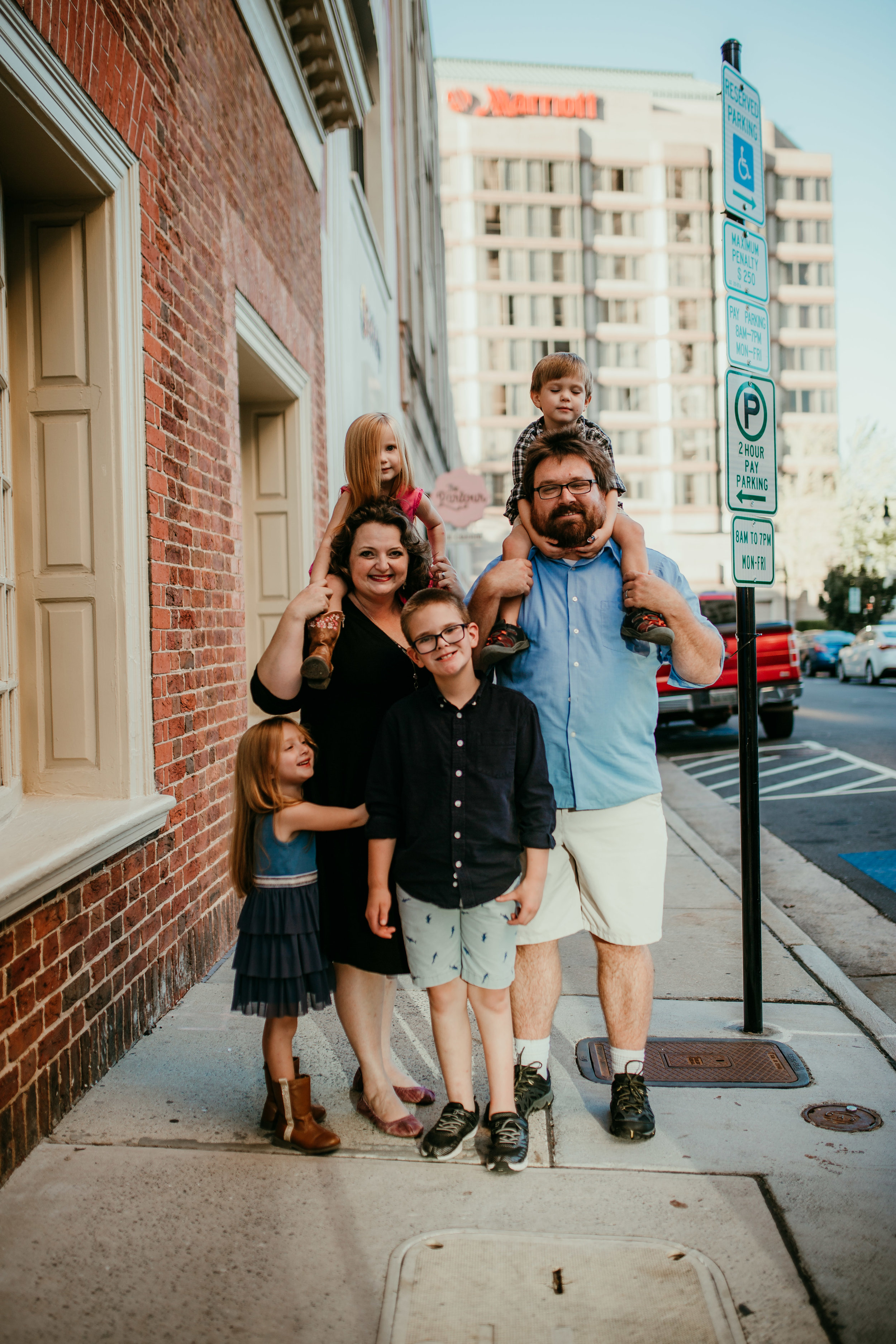 a sweet full family moment on the streets of downtown durham, NC during a fun family photography session | Hanna Hill photography | Raleigh birth and family photographer