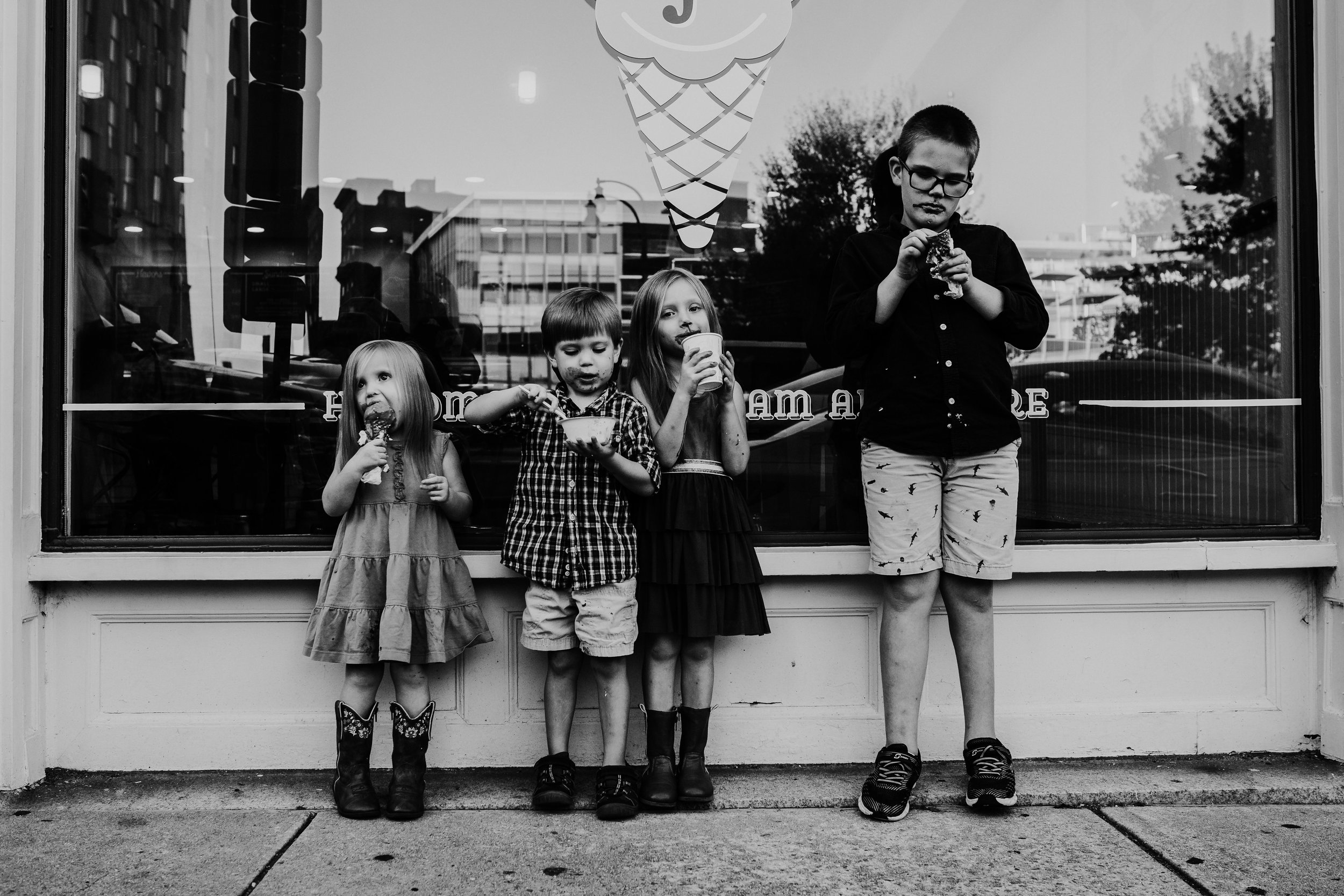 the siblings all enjoy their ice cream in front of the window during their downtown durham family photography session | Hanna Hill Photography | Raleigh birth and family photographer