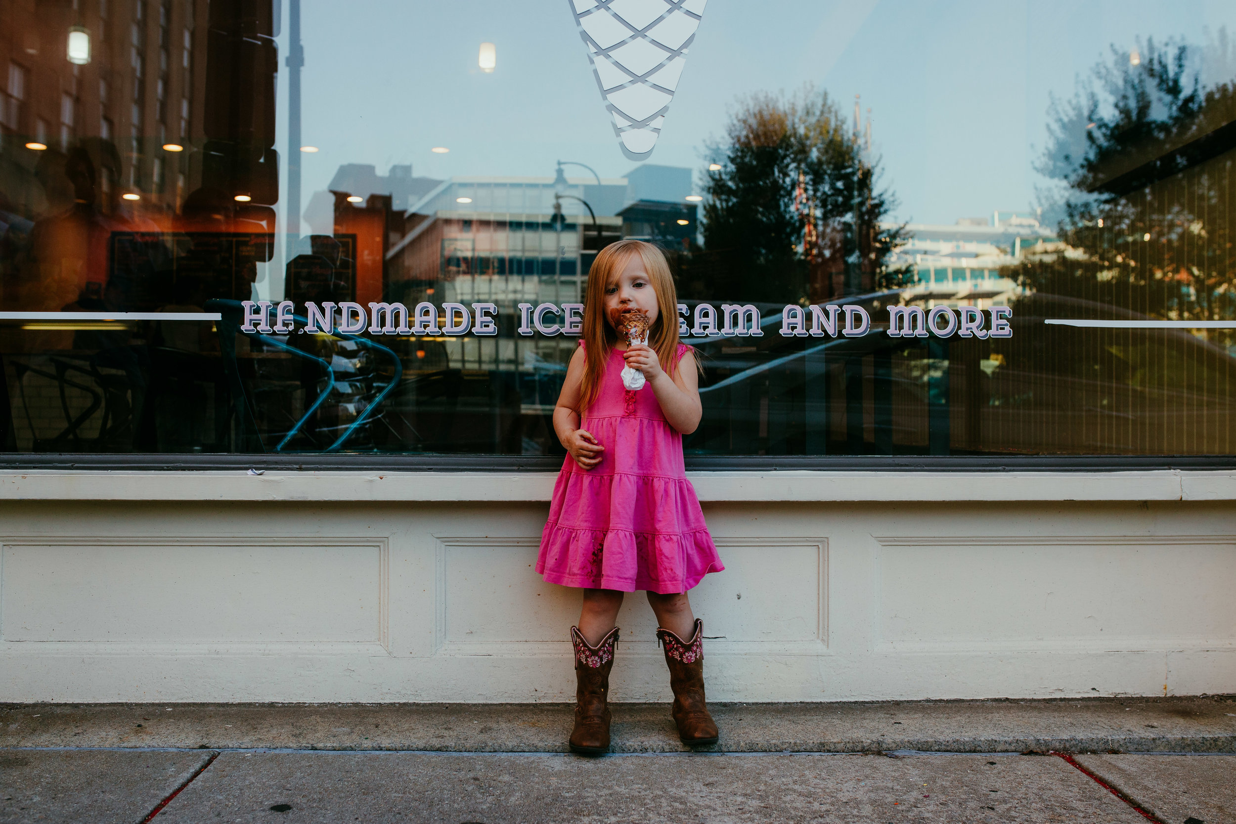 little girl eating her ice cream standing in front of a window during her downtown durham, NC family photography session | Hanna Hill Photography | Raleigh birth and family photographer