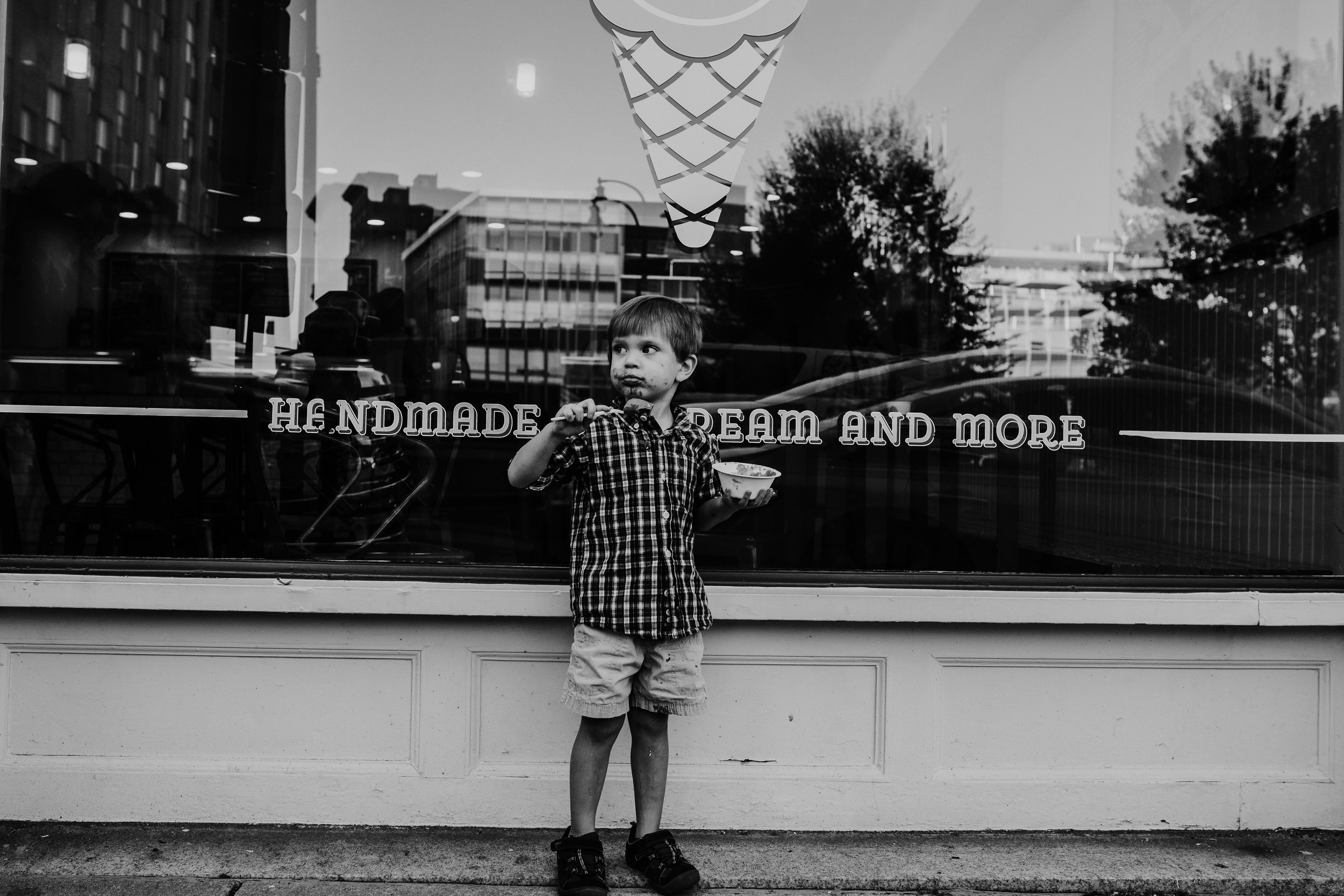 little boy eating ice cream in front of the window during a downtown durham, NC family photography session | hanna Hill photography | Raleigh birth and family photographer