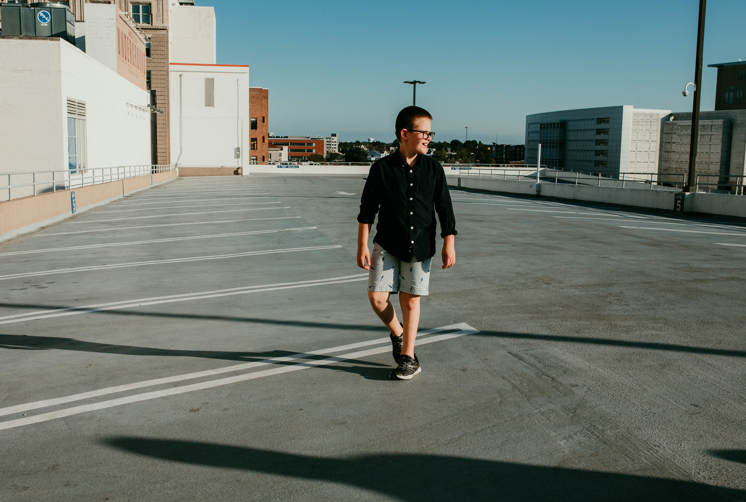 the oldest son walks along the parking deck during a downtown durham, NC | Hanna Hill Photography | Raleigh birth and family photographer