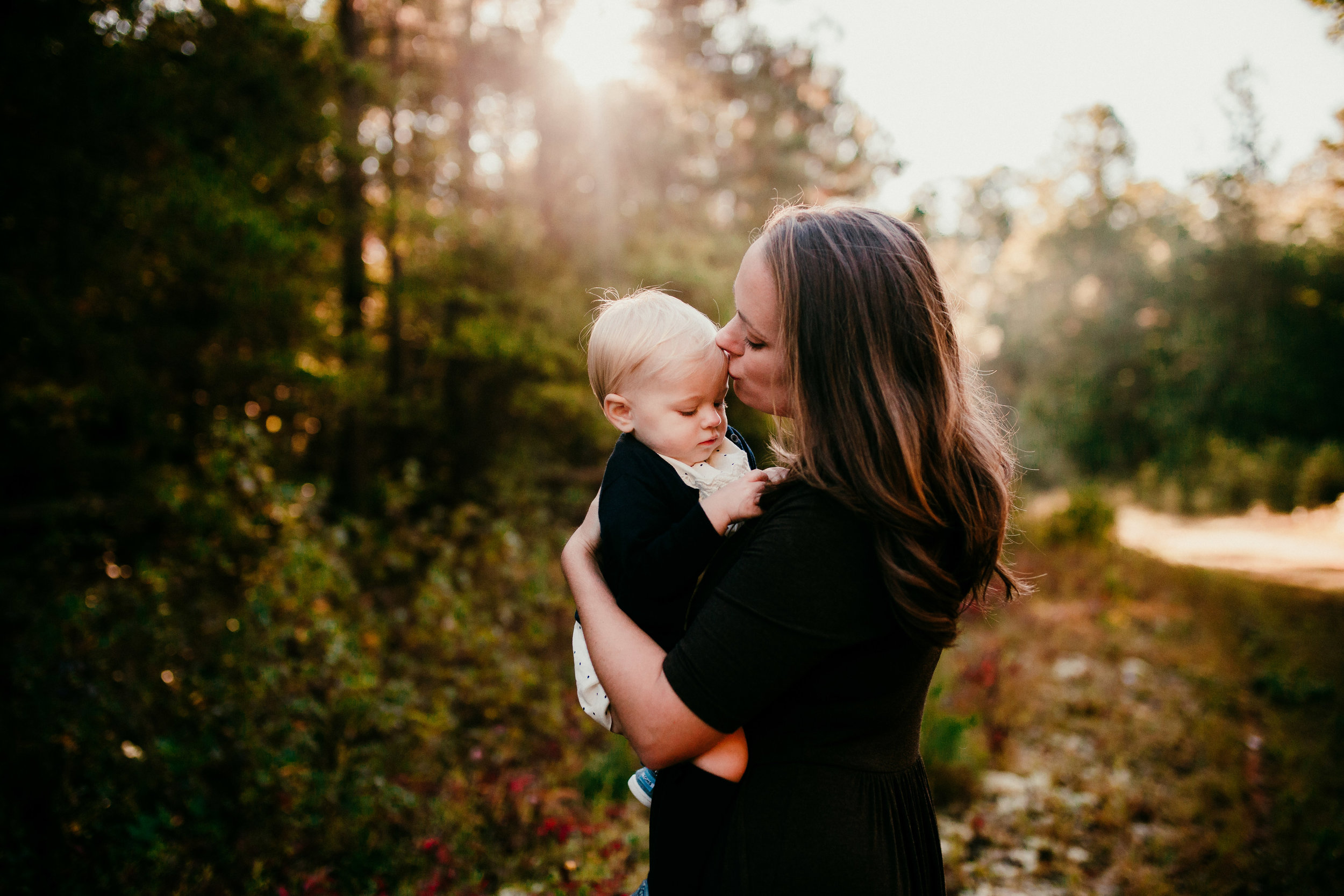a sweet motherhood moment while kissing her little girl on the forehead| Durham, NC Family Photography | Hannahill photography | Brumley nature Preserve