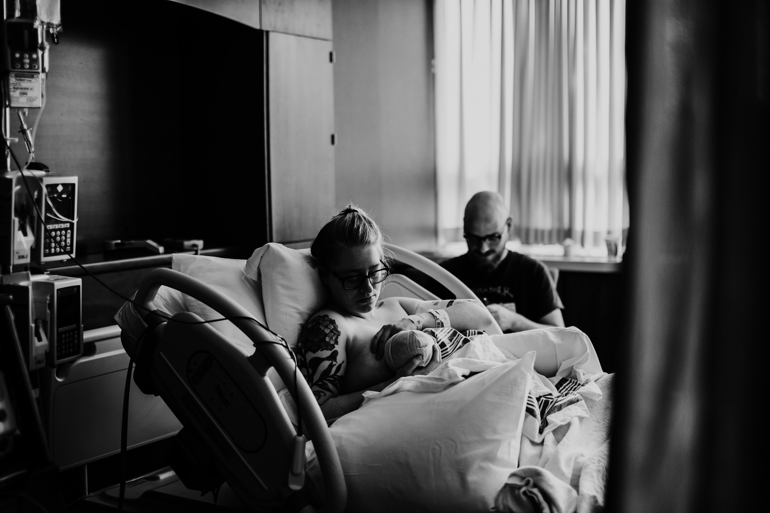 mom and baby work through breast feeding there in the hospital room while Dady texts in excitement the news of their baby | Hospital birth story Duke Regional Medical Center | North Carolina birth photography | Titus L Birth Story | Hanna Hill Photography | Raleigh Durham Birth and Family Photographer