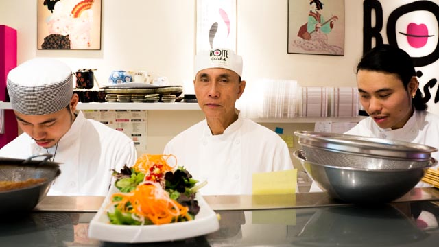 Twins Viet (right) and Nam (left) prepare sushi alongside their father.