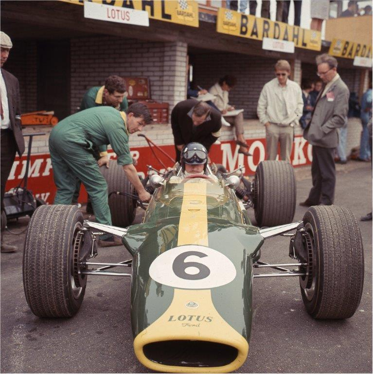Graham Hill in the pits during practice in Lotus 49/2. Standing on the right my former colleague at The Motor, the delightful author and car historian Cyril Posthumus . Photo © Eric Dymock