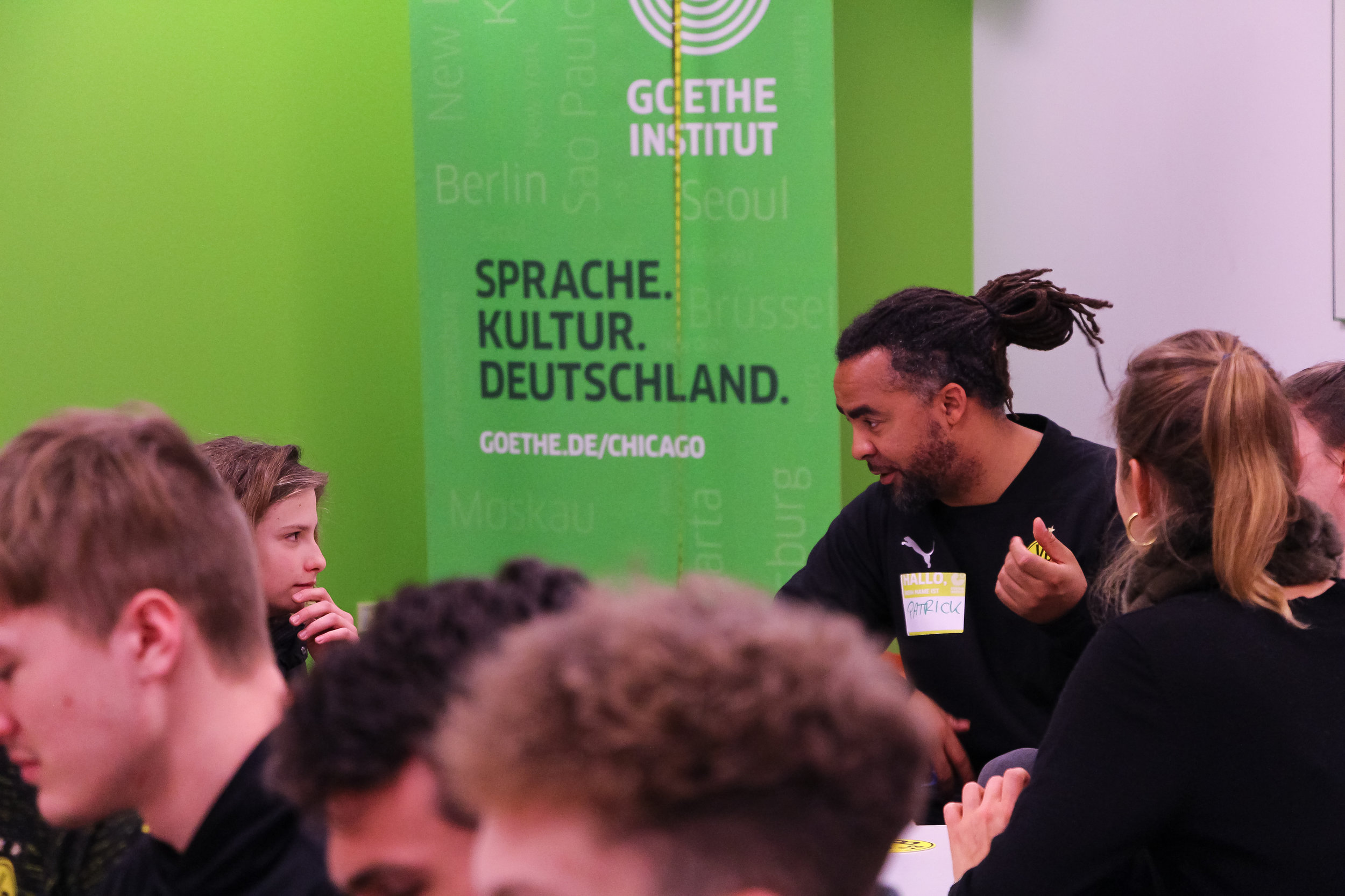 Former Borussia Dortmund and German National Football Team player Patrick Owomoyela chats with a student. Goethe-Institut, Chicago, 2019.