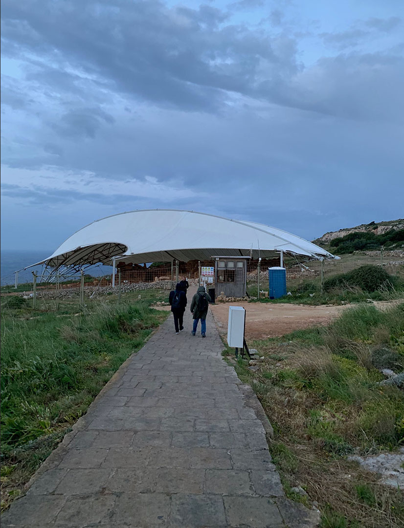 Walking down the visitors' path to Mnajdra Temple, which is protected from the weather by a canopy. The sea is visible in the distance.