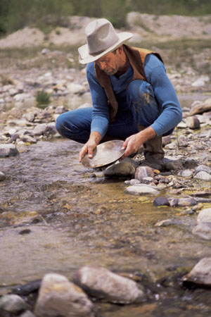 Photo of modern gold prospector panning for gold to send to GoldRefiners.com for smelting and refining.
