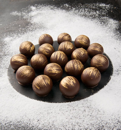 Photo of gold-dusted chocolates for Gold Refiners blog post about what you need to know about eating gold. Credit: Madiz/iStock.