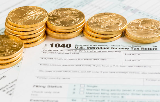 Photo of gold coins on an IRS Tax Form 1040 for a blog post about paying taxes on found gold. Credit: BackyardProduction/iStock.