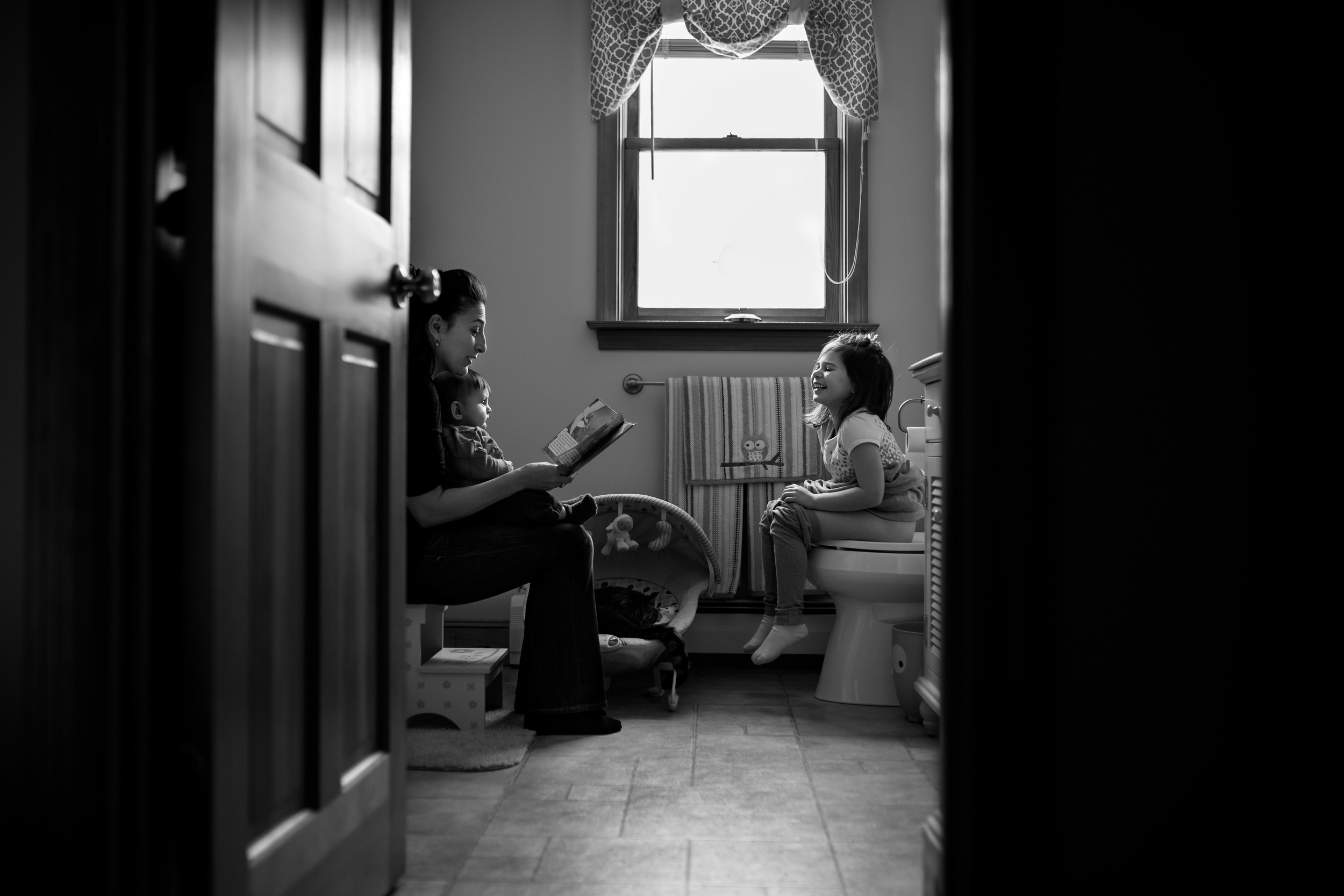 Mom Reading To Daughter On Toilet