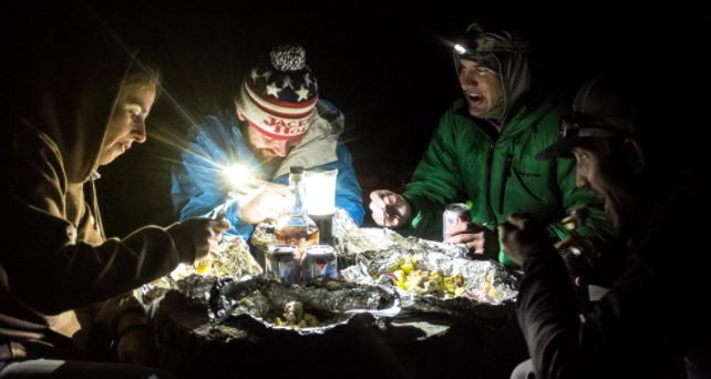 The author (left) eats dinner by headlamp with Patrick Dorgan, Steven Brutger, and Josh Peterson.