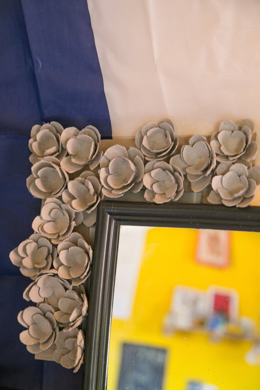 Mirror and Framing             Cost: Ate some eggs  What I Used: Egg trays, scissors, a hot glue gun, and cardboard.