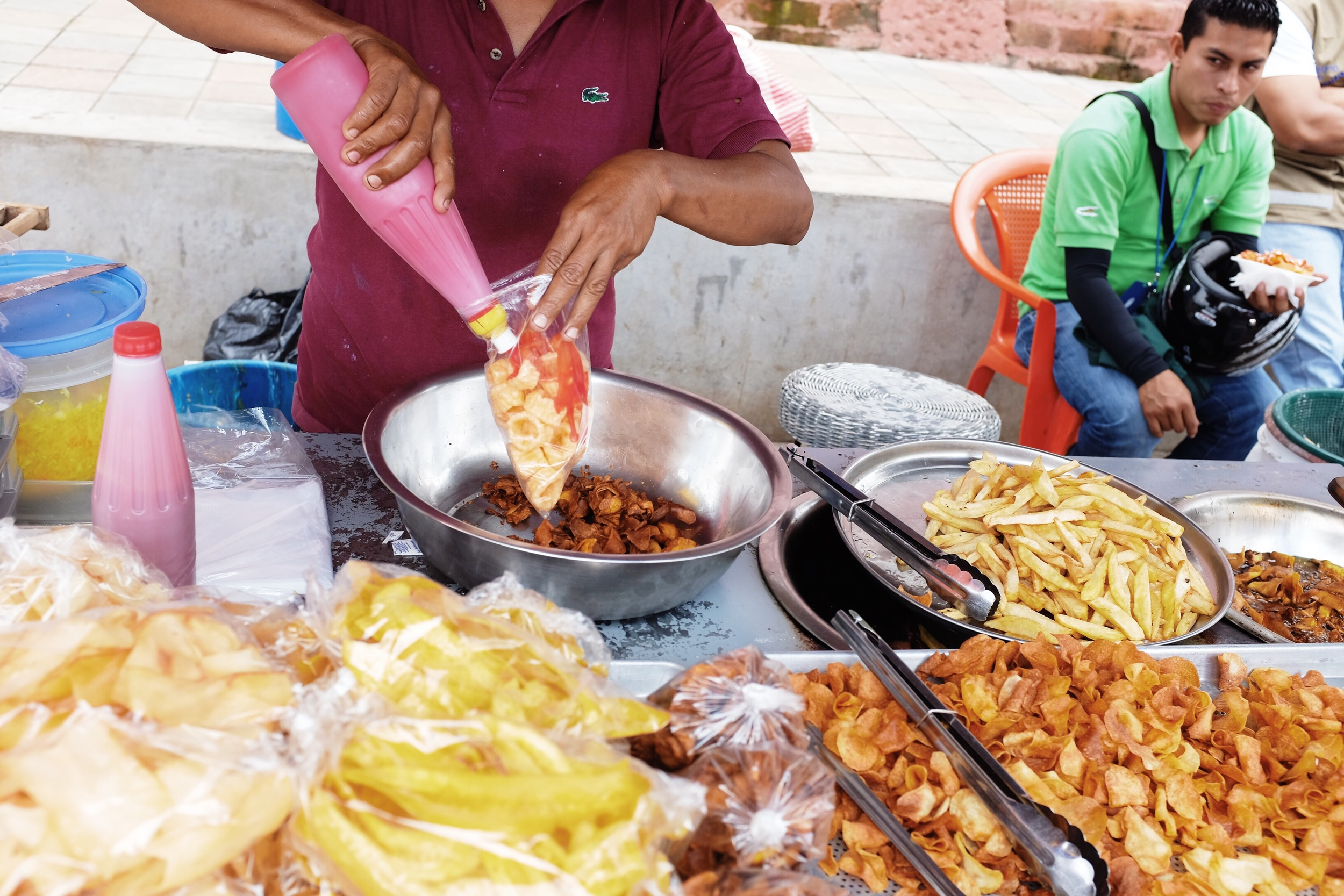 A display of popular snacks such as fried pork skin, yucca chips, and plantain chips.