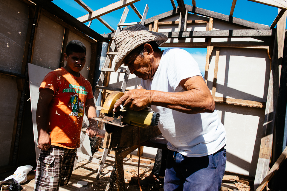 A local Isla la Pirraya man and two friends work on building a new house on pylons over the water.