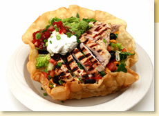 Tortilla bowl filled with chicken & salsa and topped with Mexican Guacamole