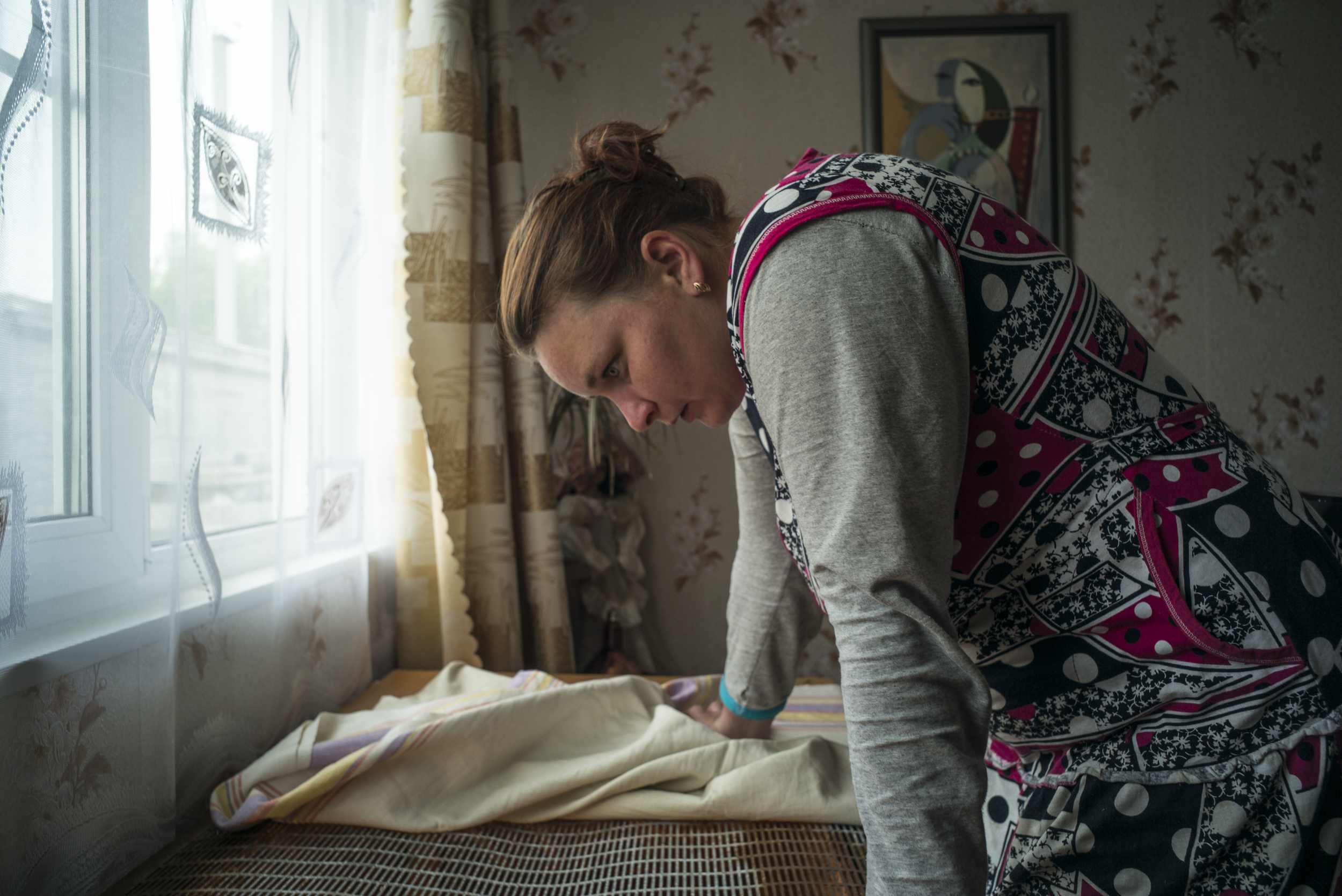 Sevetlana Taherbeigi prepares for yet another day on the farm at the crack of dawn on Tuesday morning, June 2, 2015, in Goritsa, Moskovskaya, Russia. She had stayed up almost all night drinking vodka with her mother and husband because her children were out of town. (© Alicia Afshar)